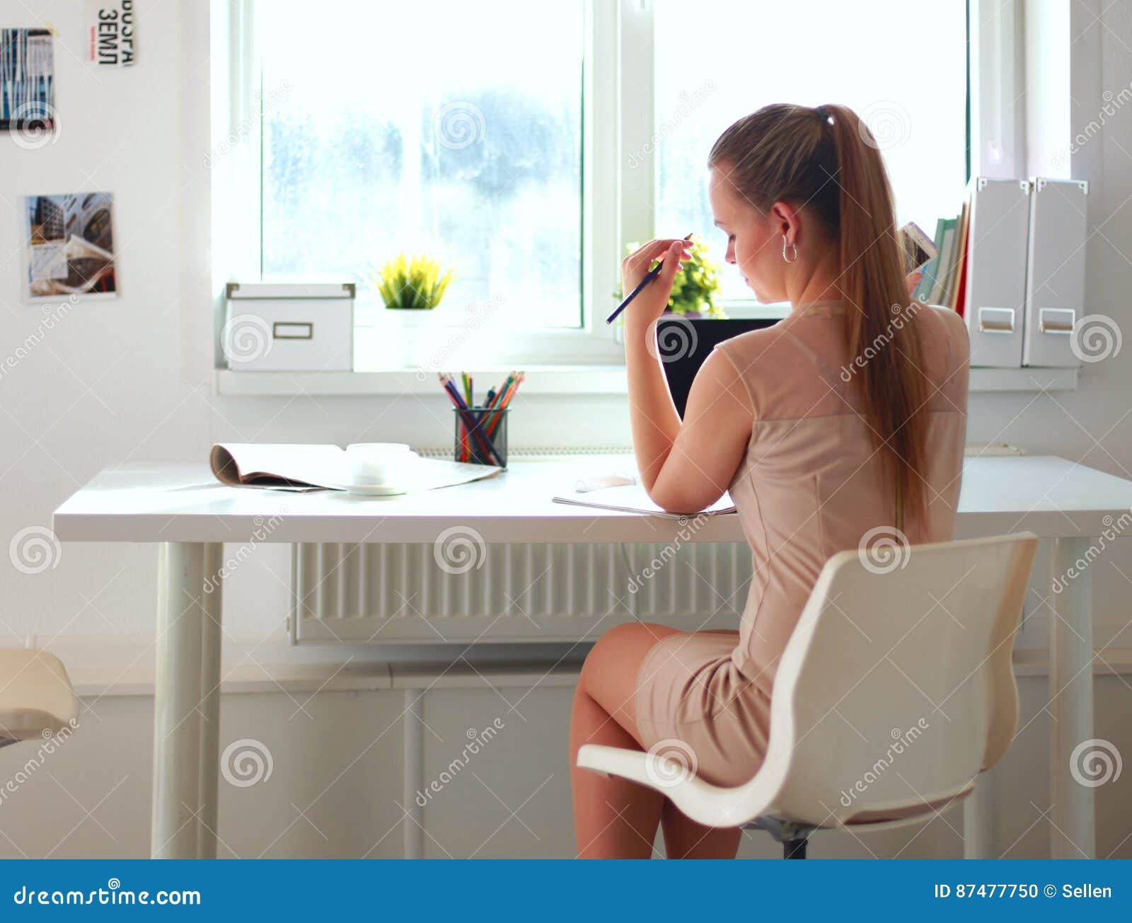 Женщина при документы сидя на столе и компьтер-книжке