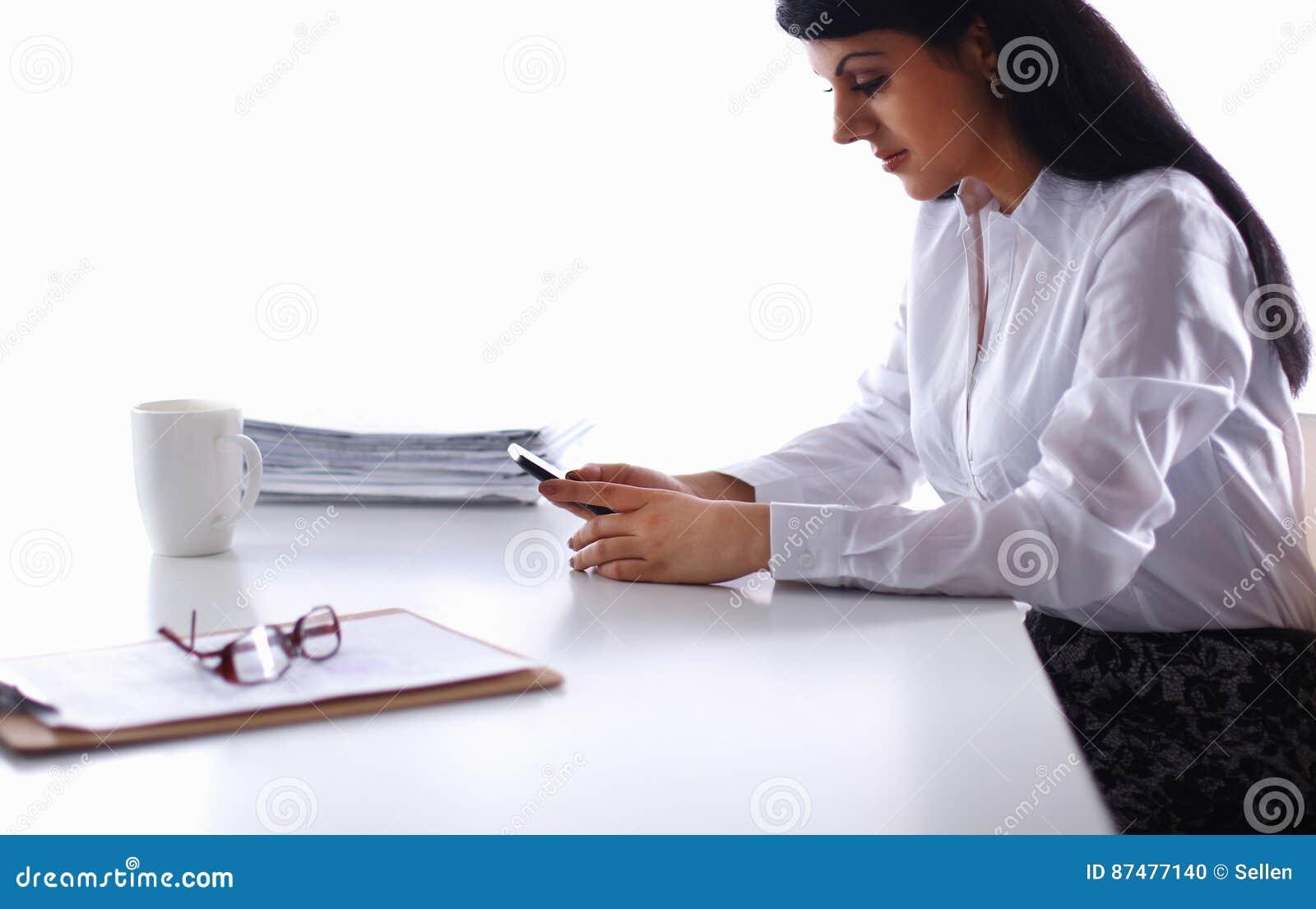 Женщина при документы сидя на столе