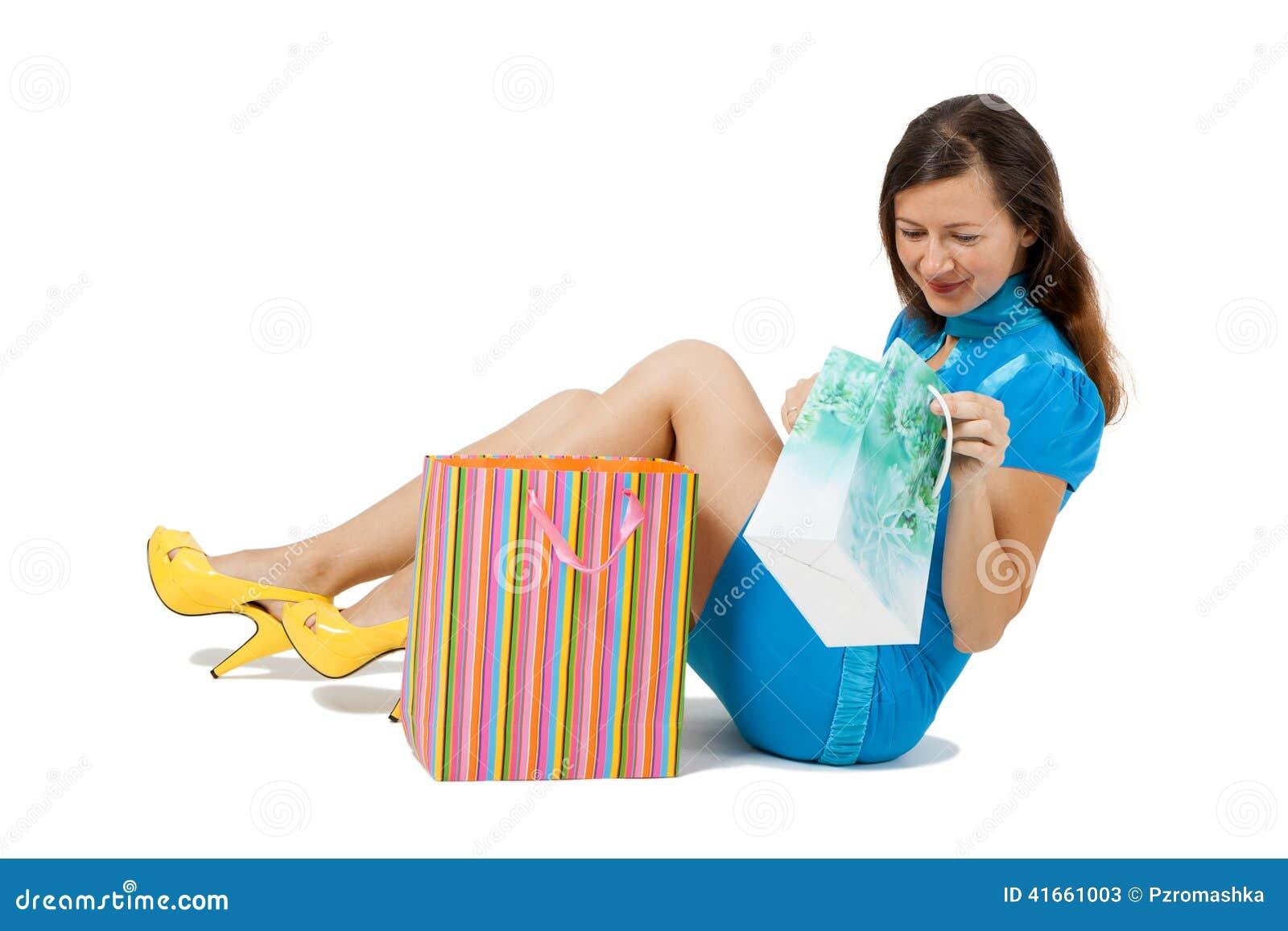 Женщина при пакеты сидя на поле