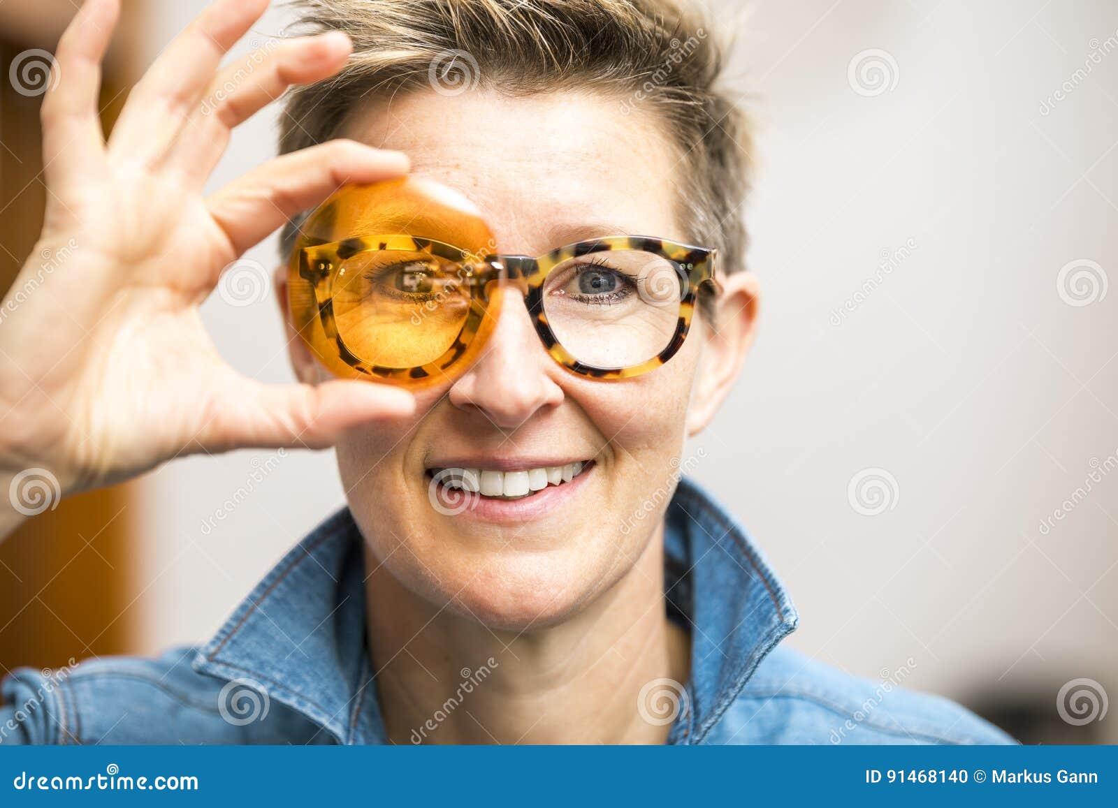 Женщина при стекла смотря через оранжевое стекло