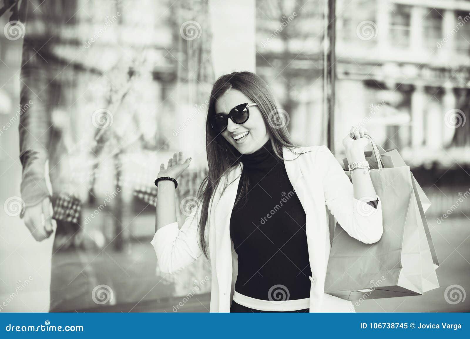 Женщина при хозяйственные сумки входя в магазин