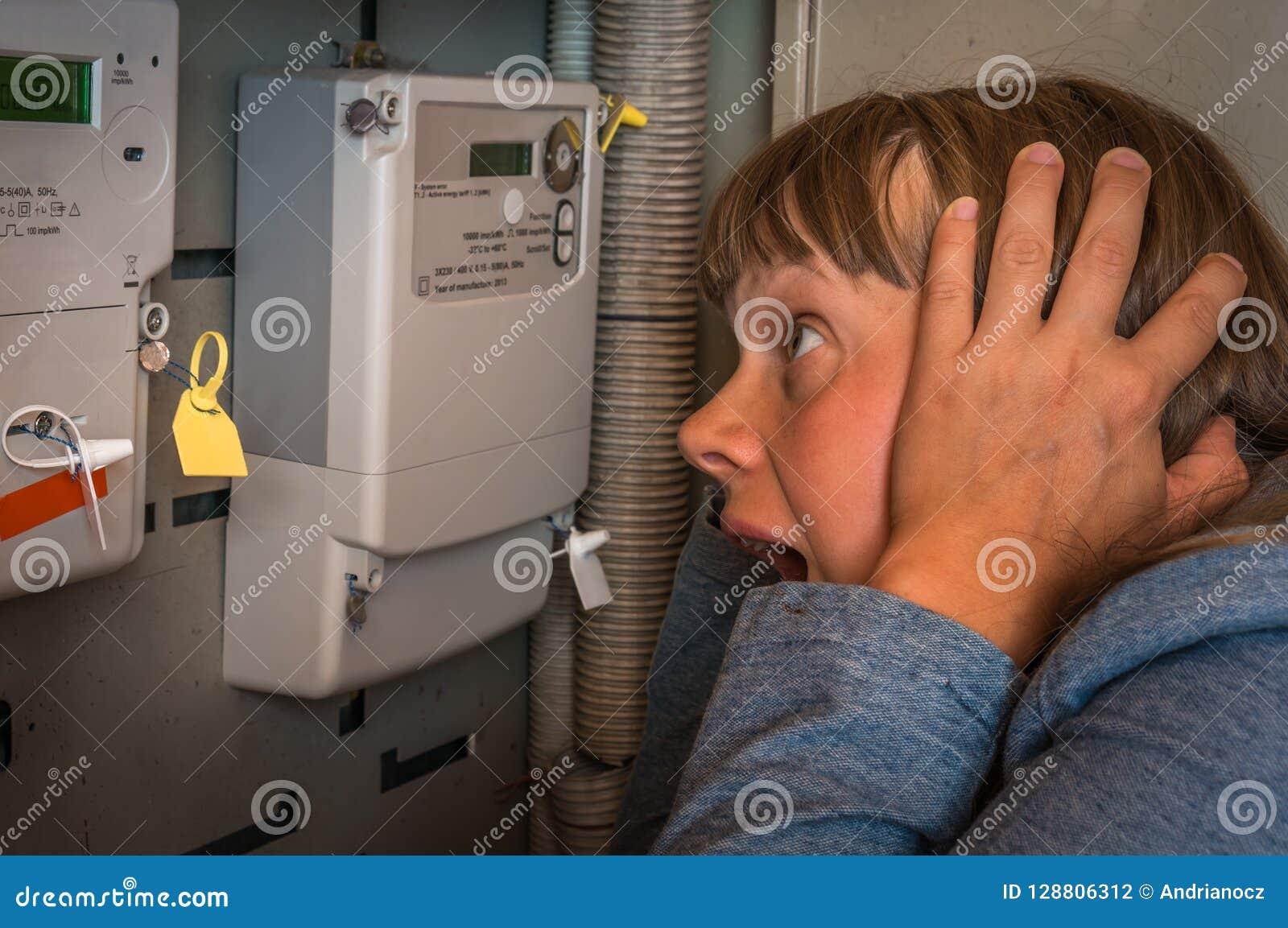 Женщина проверяет метр электричества - дорогое электричество conc