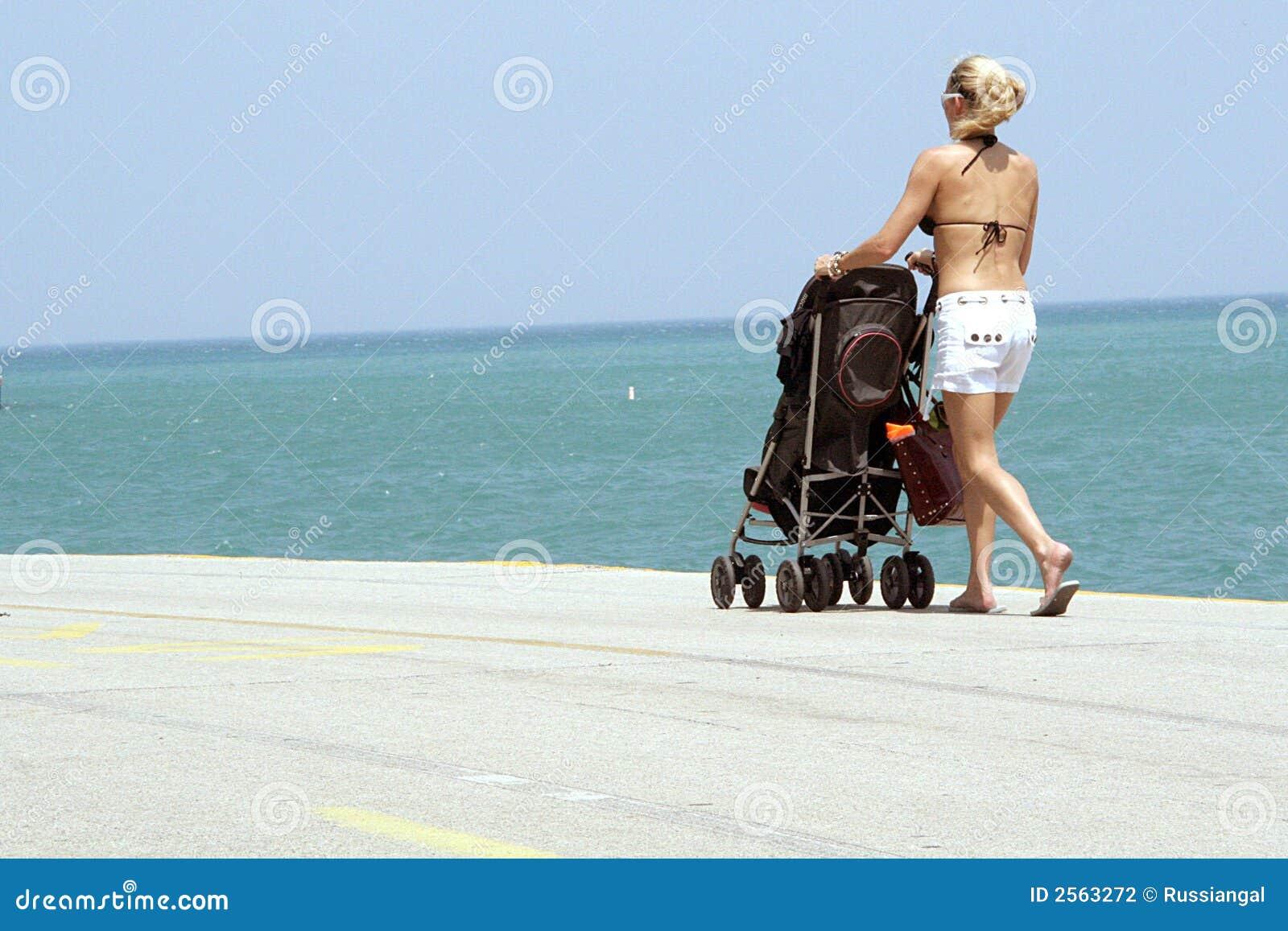 женщина прогулочной коляски пляжа