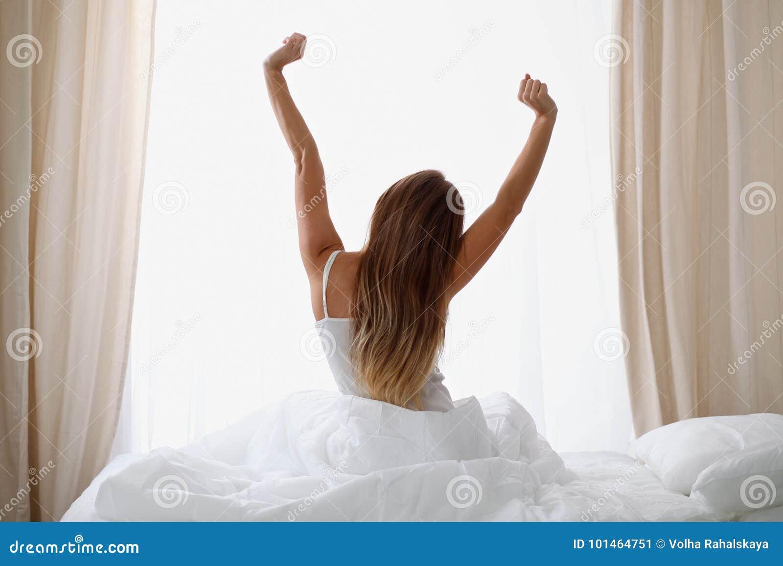 Женщина протягивая в кровати после бодрствования вверх, заднего взгляда, входя в день счастливый и расслабленный после сна спокой