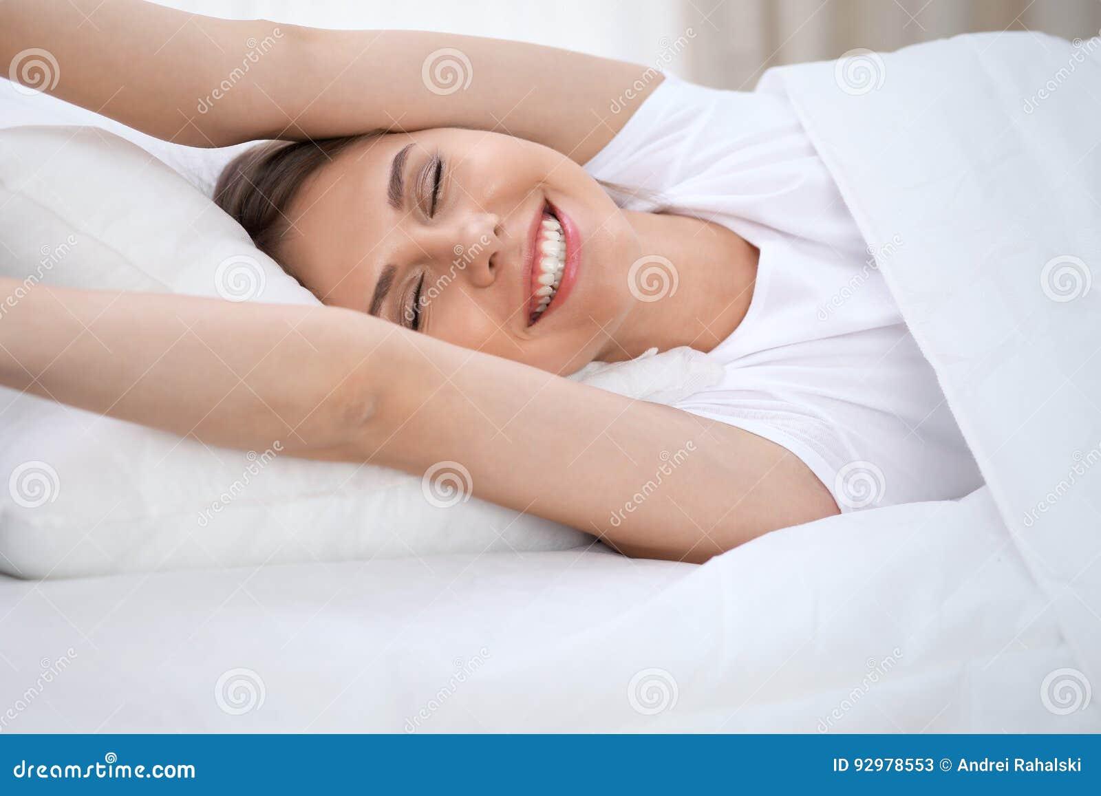 Женщина протягивая в кровати после бодрствования вверх, входящ в день счастливый и расслабленный после сна спокойной ночи Сладост