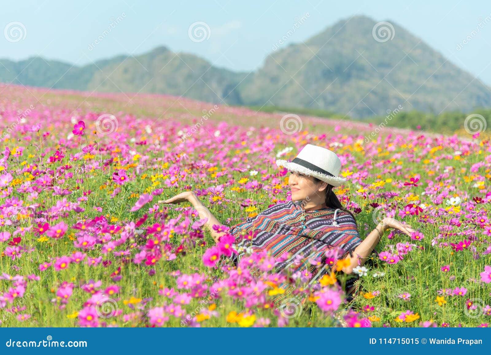 Женщина путешественника азиатская ослабляет и свобода в красивом зацветая цветочном саде космоса