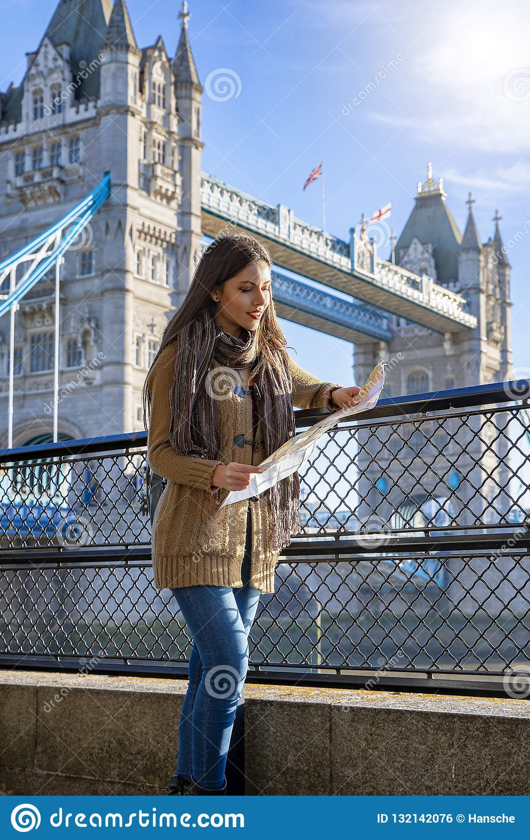 Женщина путешественника держит карту перед мостом Лондоном башни