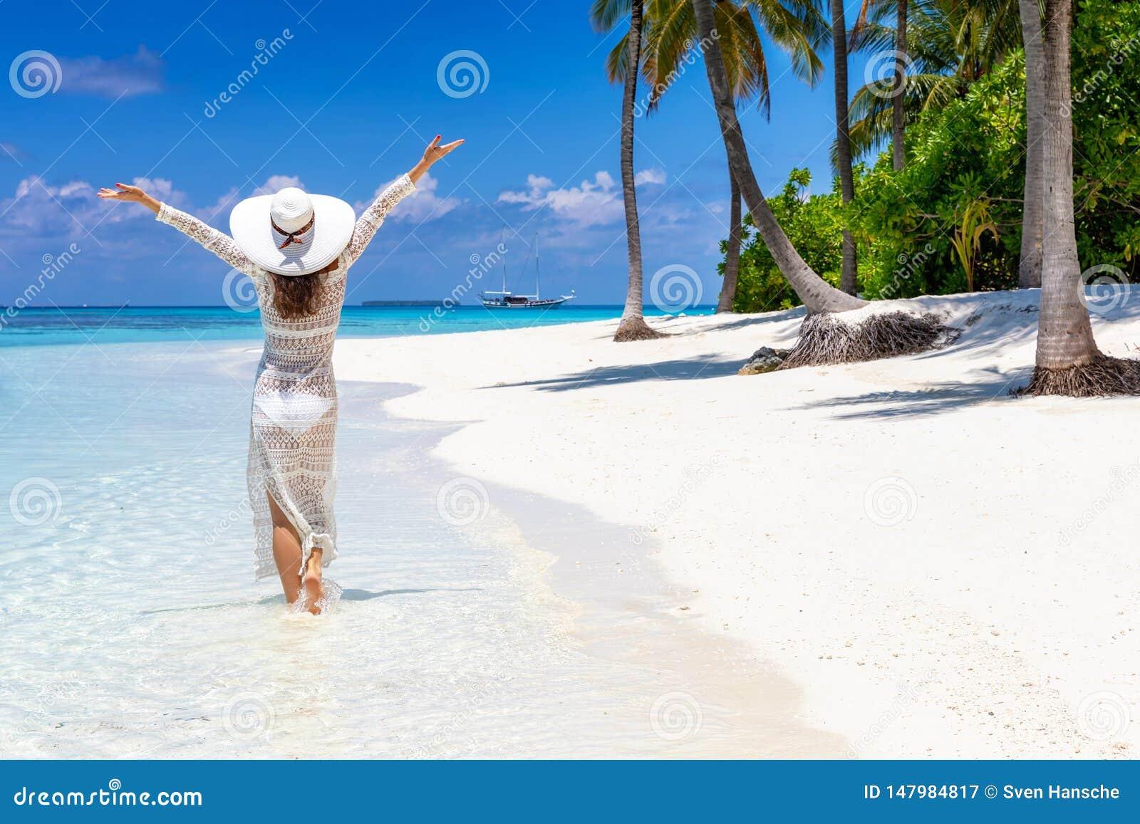 Женщина путешественника наслаждается ее тропическими каникулами пляжа
