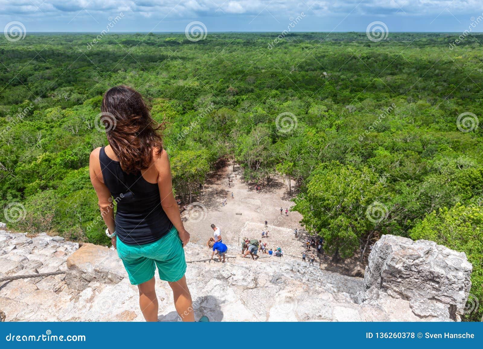 Женщина путешественника смотрит пирамиду Nohoch Mul в Coba, Юкатан, Мексике
