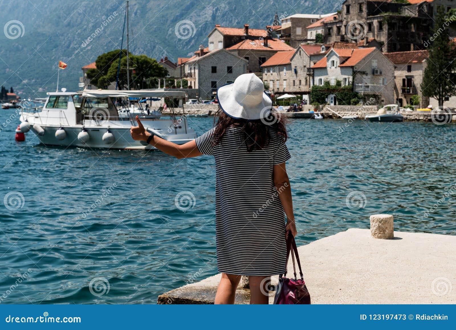 Женщина путешествовать на пристани Девушка ждет шлюпку на пристани
