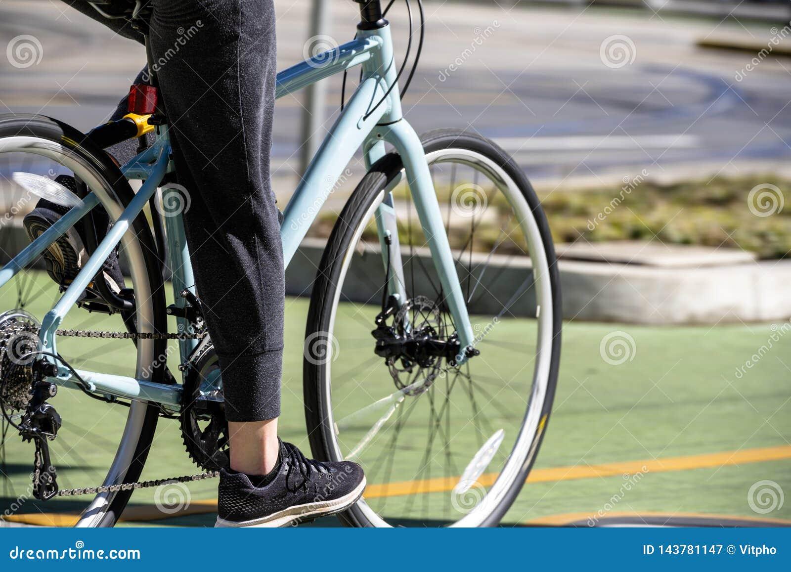 Женщина работая в езде на всеобщих классических велосипедах дороги для продвижения здоровья