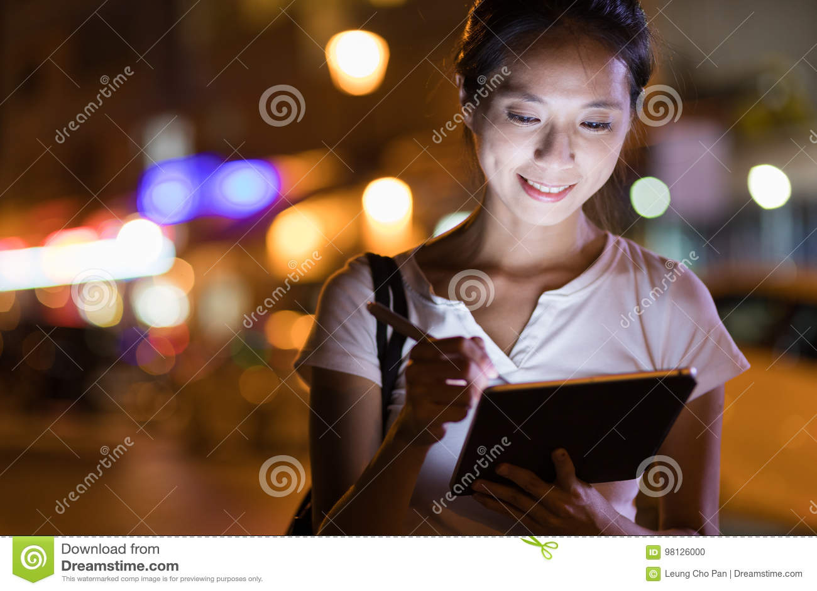 Женщина работая на цифровом планшете на ноче