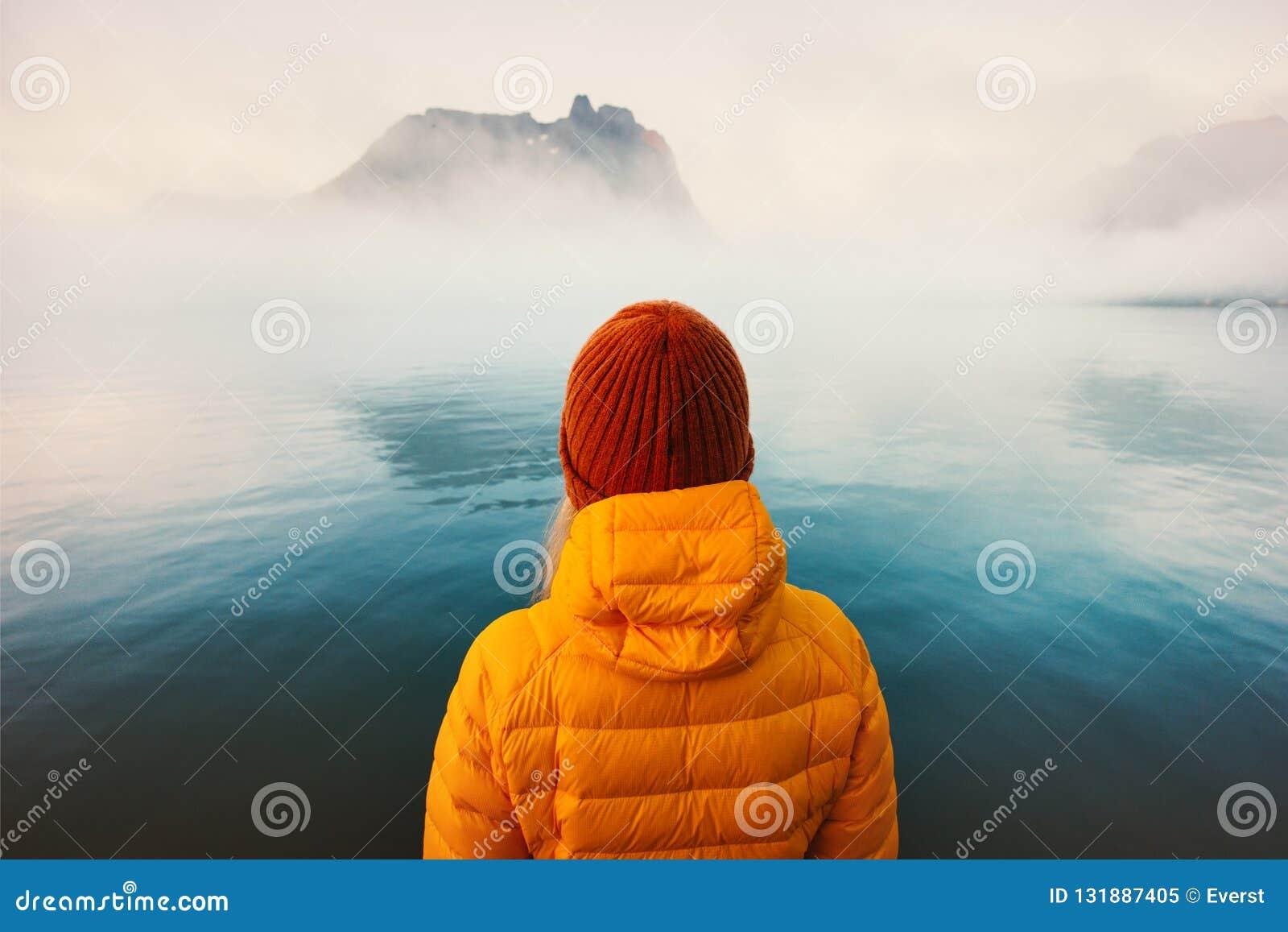 Женщина самостоятельно смотря туманное холодное море путешествуя образ жизни приключения