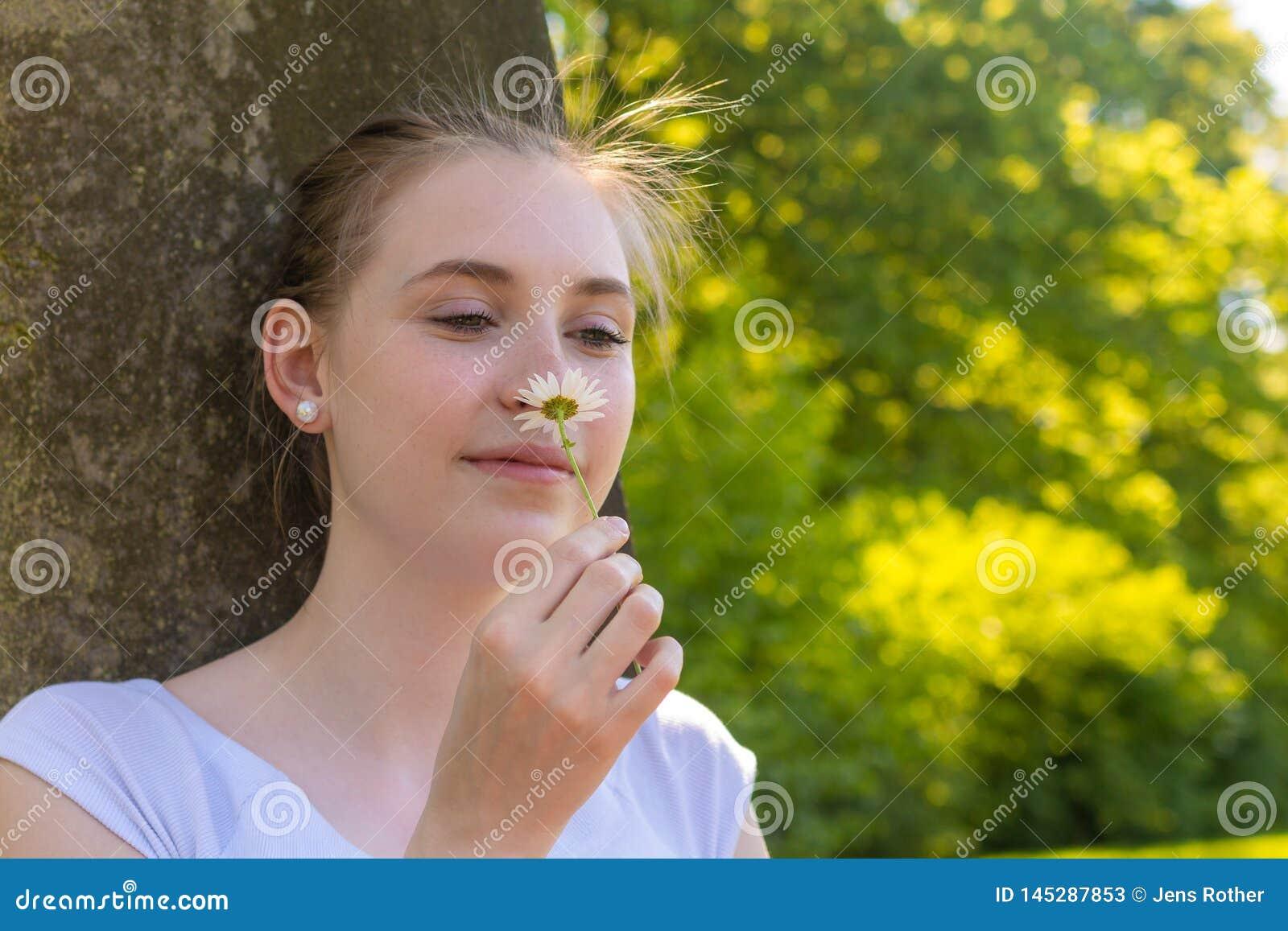Женщина сидит под деревом и пахнет на цветке