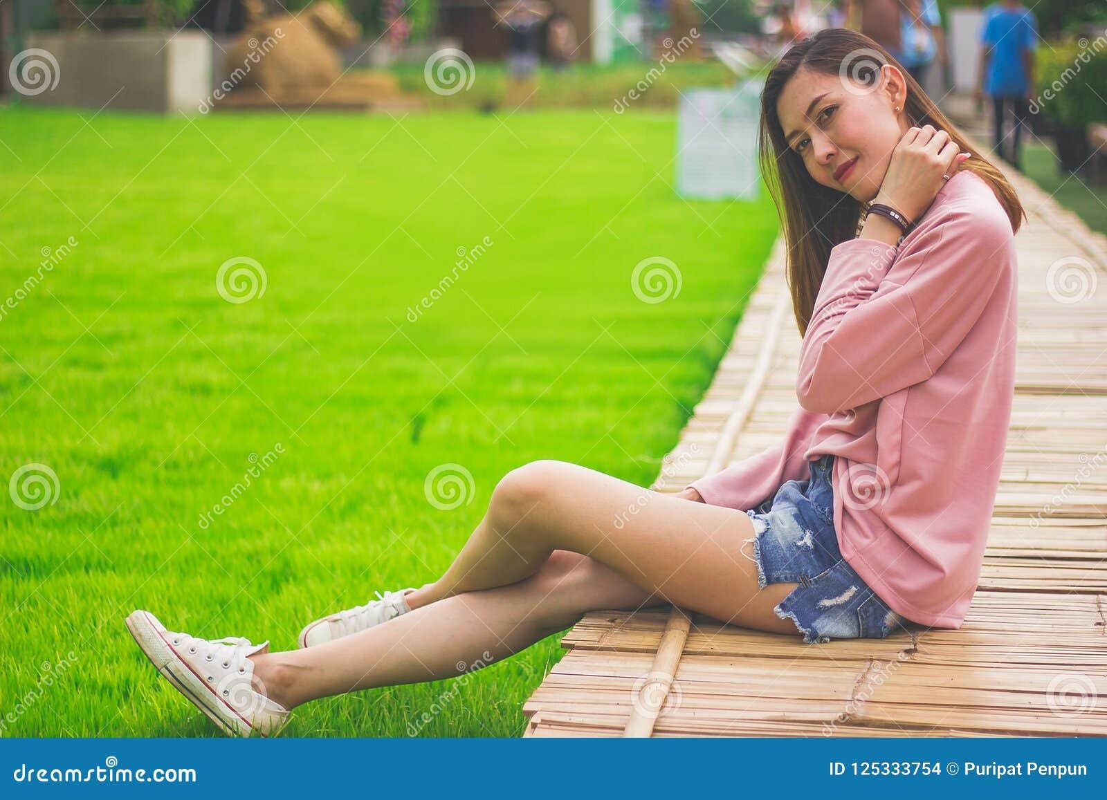 Женщина сидя на бамбуковом мосте