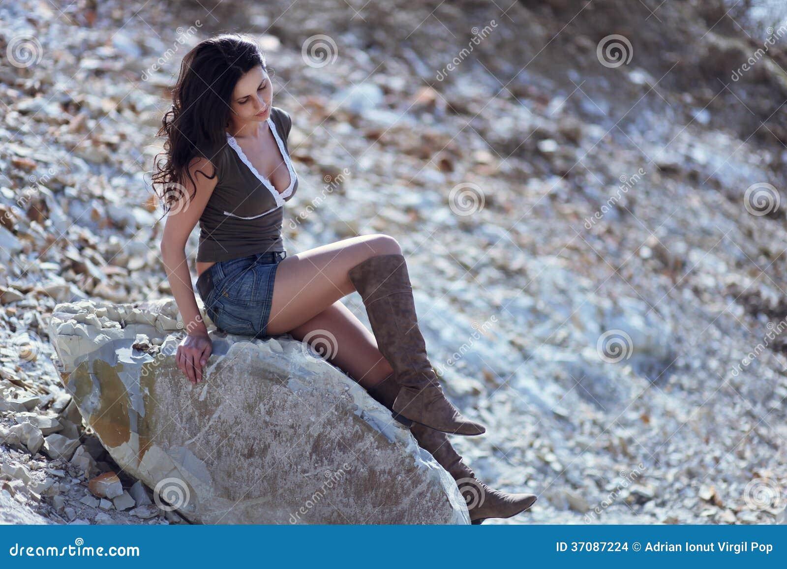 Женщина сидя на каменном валуне
