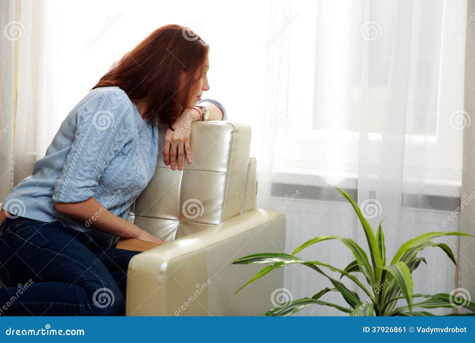 Женщина сидя на софе и смотря в окне