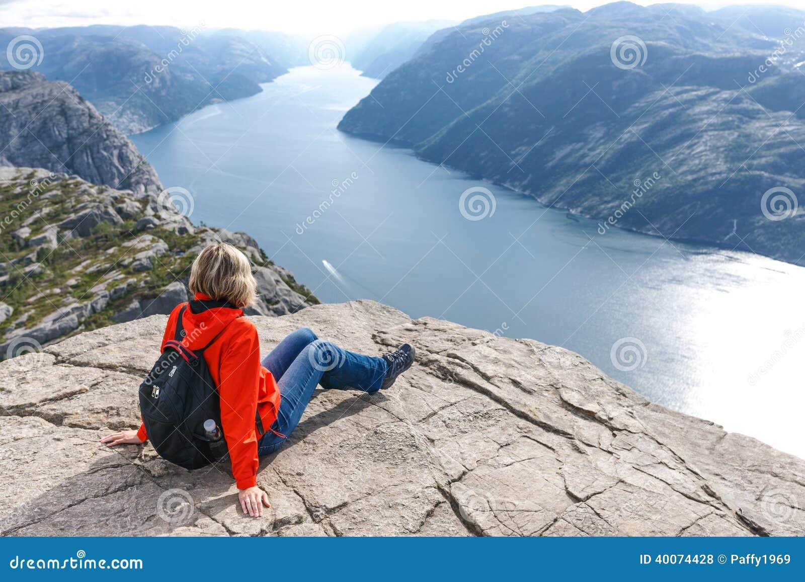 Женщина сидя на утесе амвона/Preikestolen, Норвегии