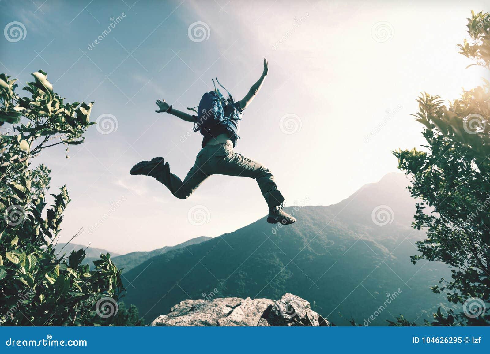 Женщина скача на край ` s скалы