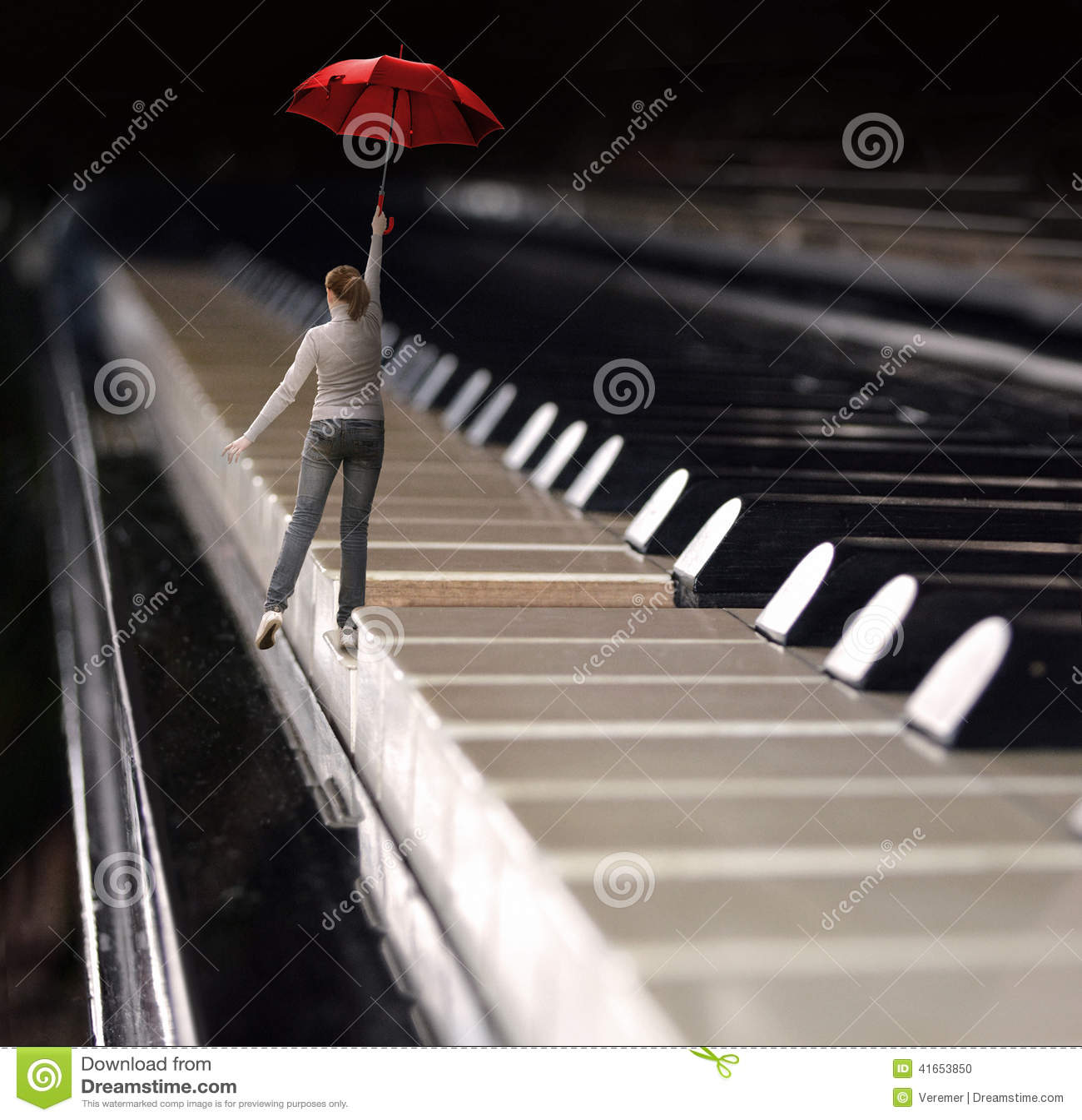 Женщина скачет с зонтиком на клавиатуре рояля