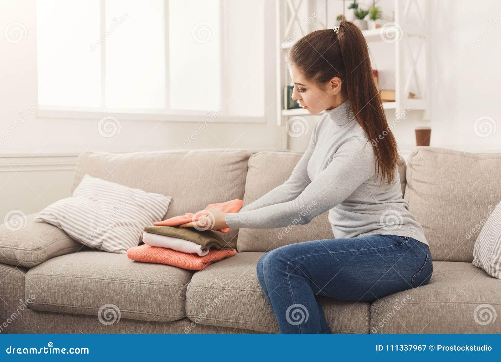 Женщина складывая чистые футболки дома