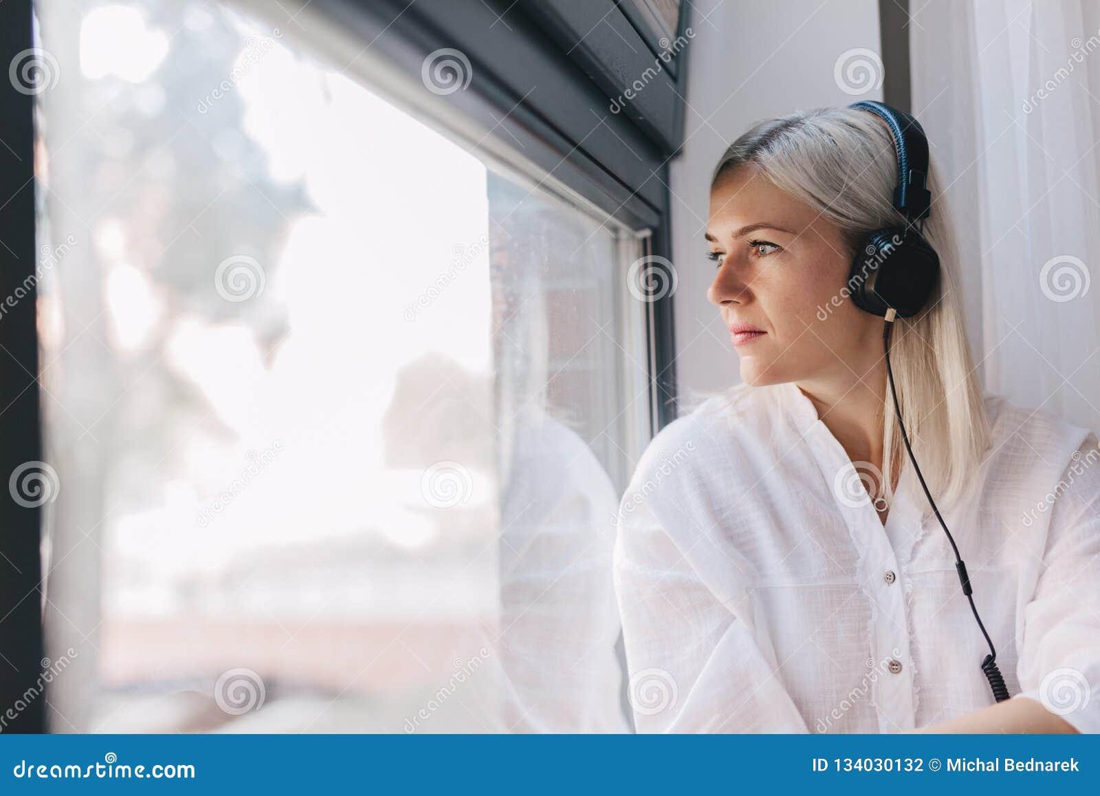 Женщина слушая музыку, смотря через окно