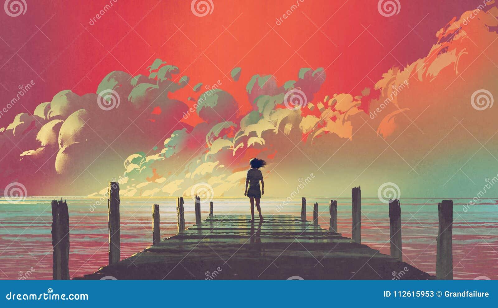 Женщина смотря красочные облака в небе