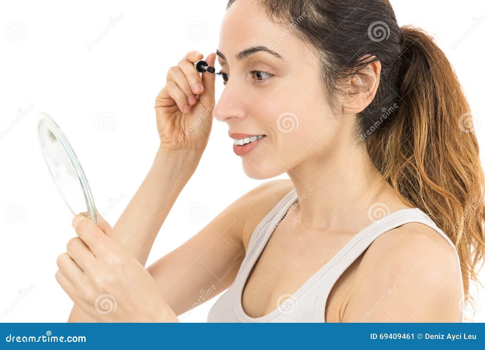 Женщина смотря к зеркалу и прикладывая тушь