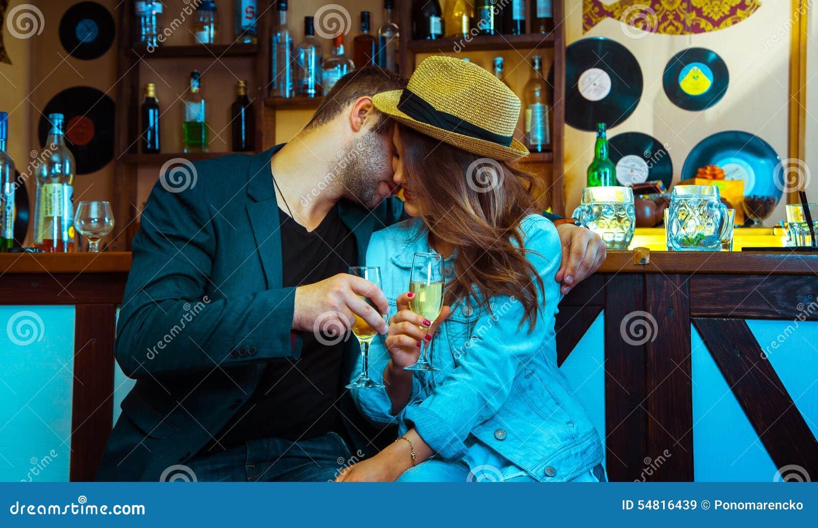 Женщина сокращая человека в баре и выпивая шампанское