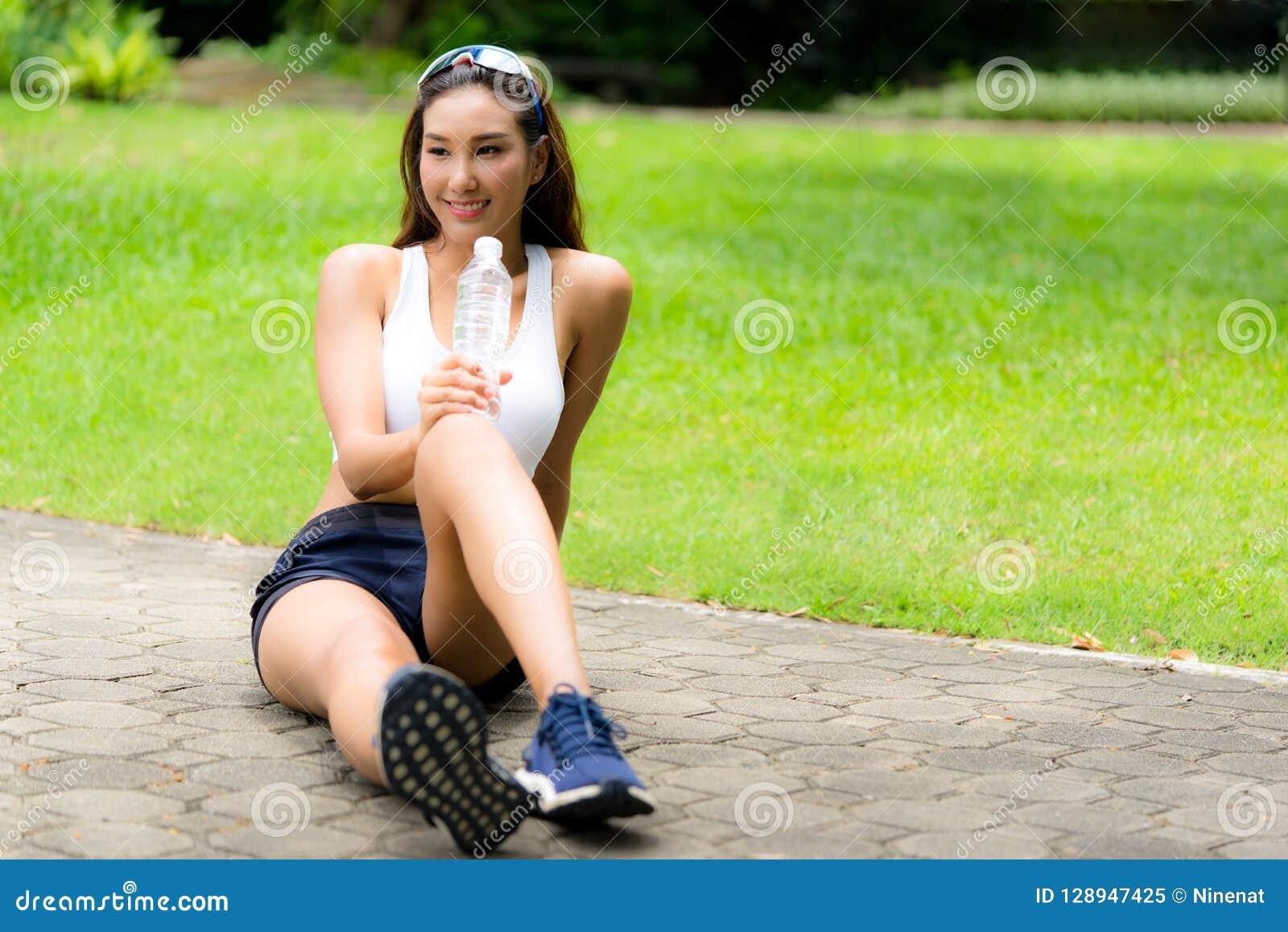 Женщина спорта Smiley красивая держа бутылку воды отдыхая после тренировки