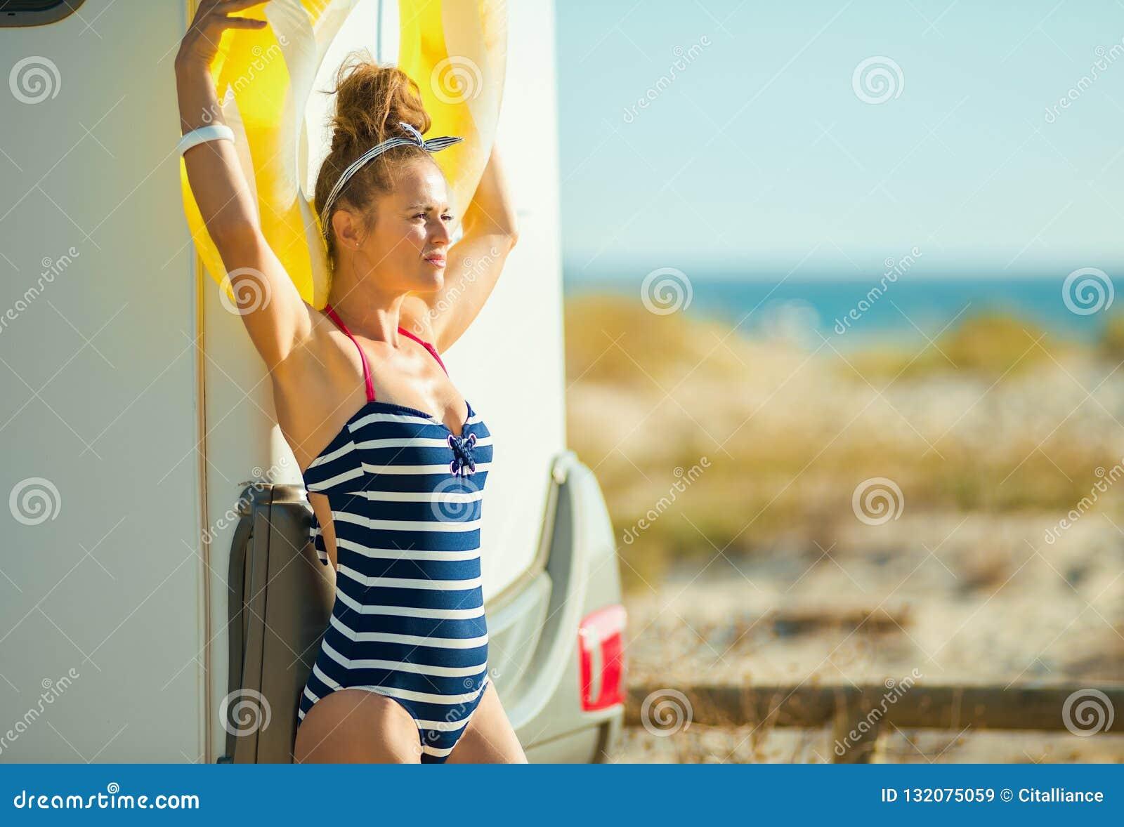 Женщина с желтый раздувной lifebuoy смотреть в расстояние