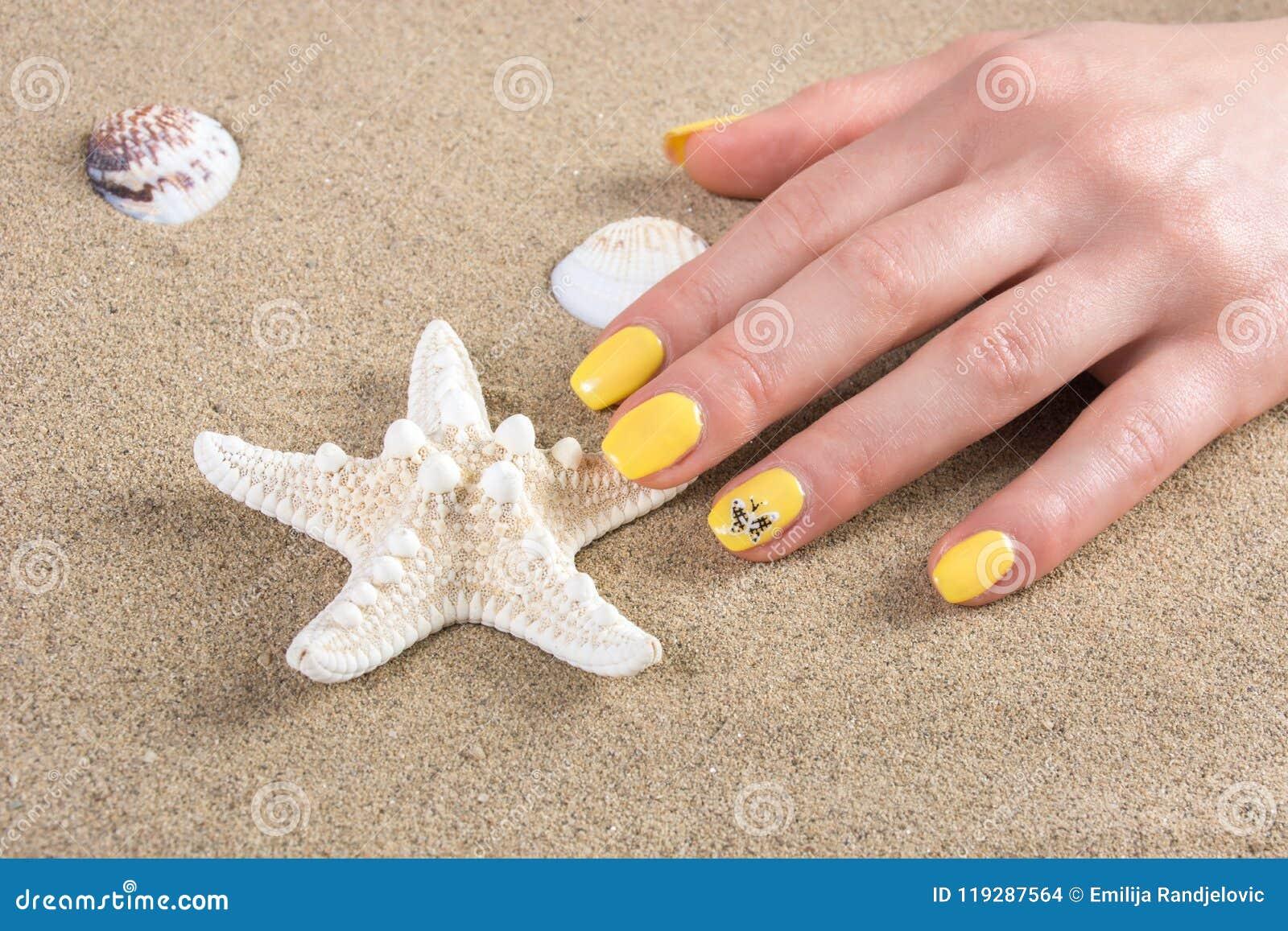 Женщина с желтыми ногтями делать морские звёзды заполированности касающие на песке моря на пляже