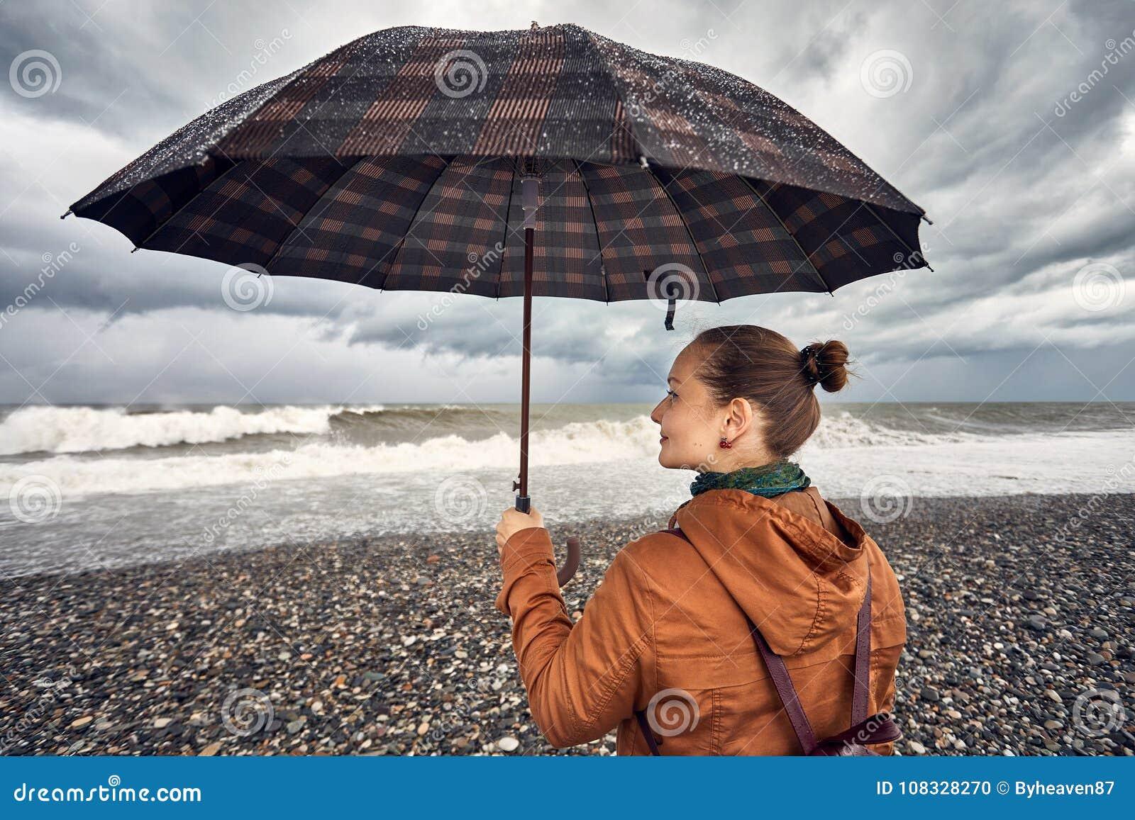 Женщина с зонтиком около бурного моря
