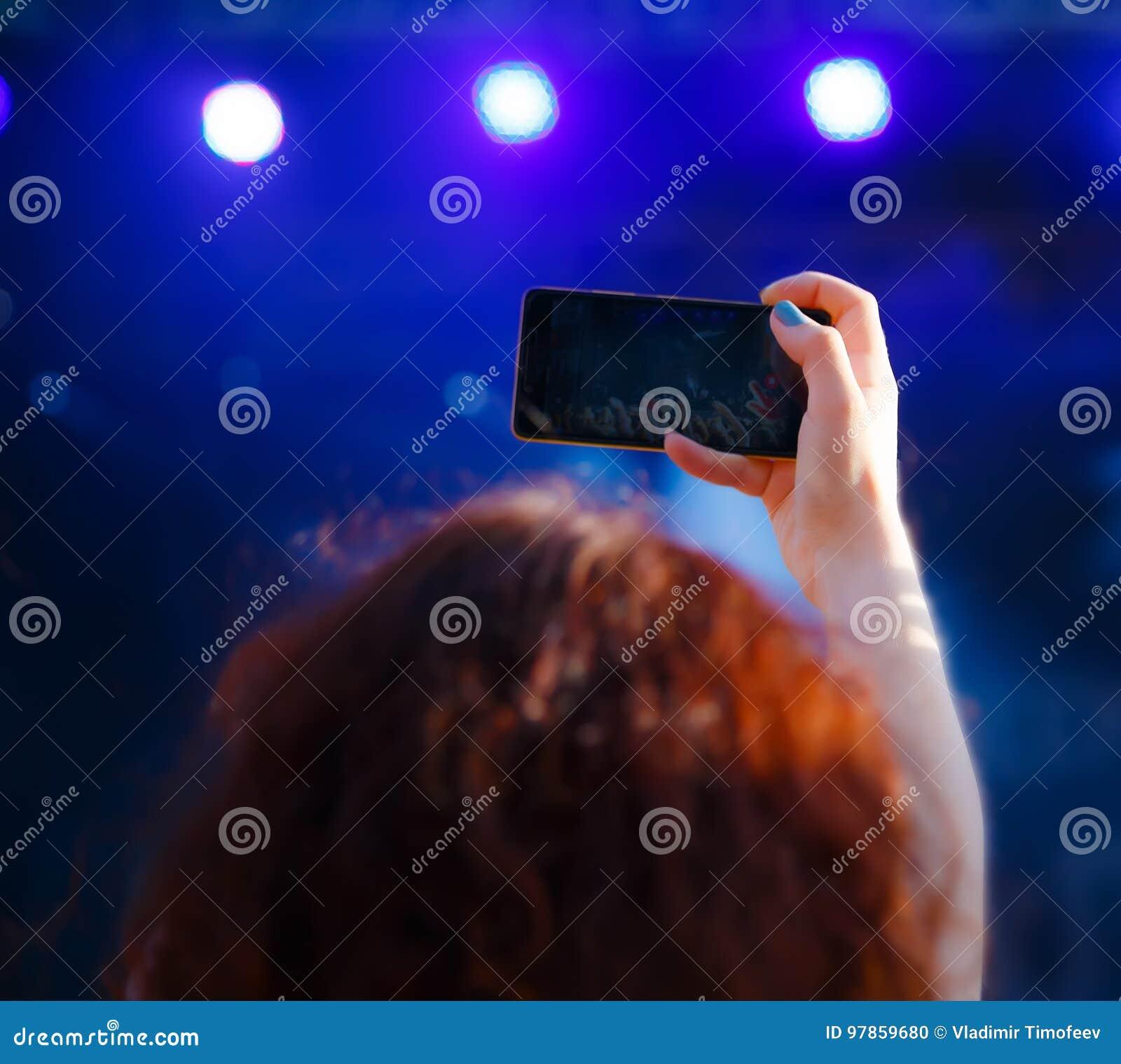 Женщина с концертом стрельбы телефона, взглядом от позади, влияние нерезкости