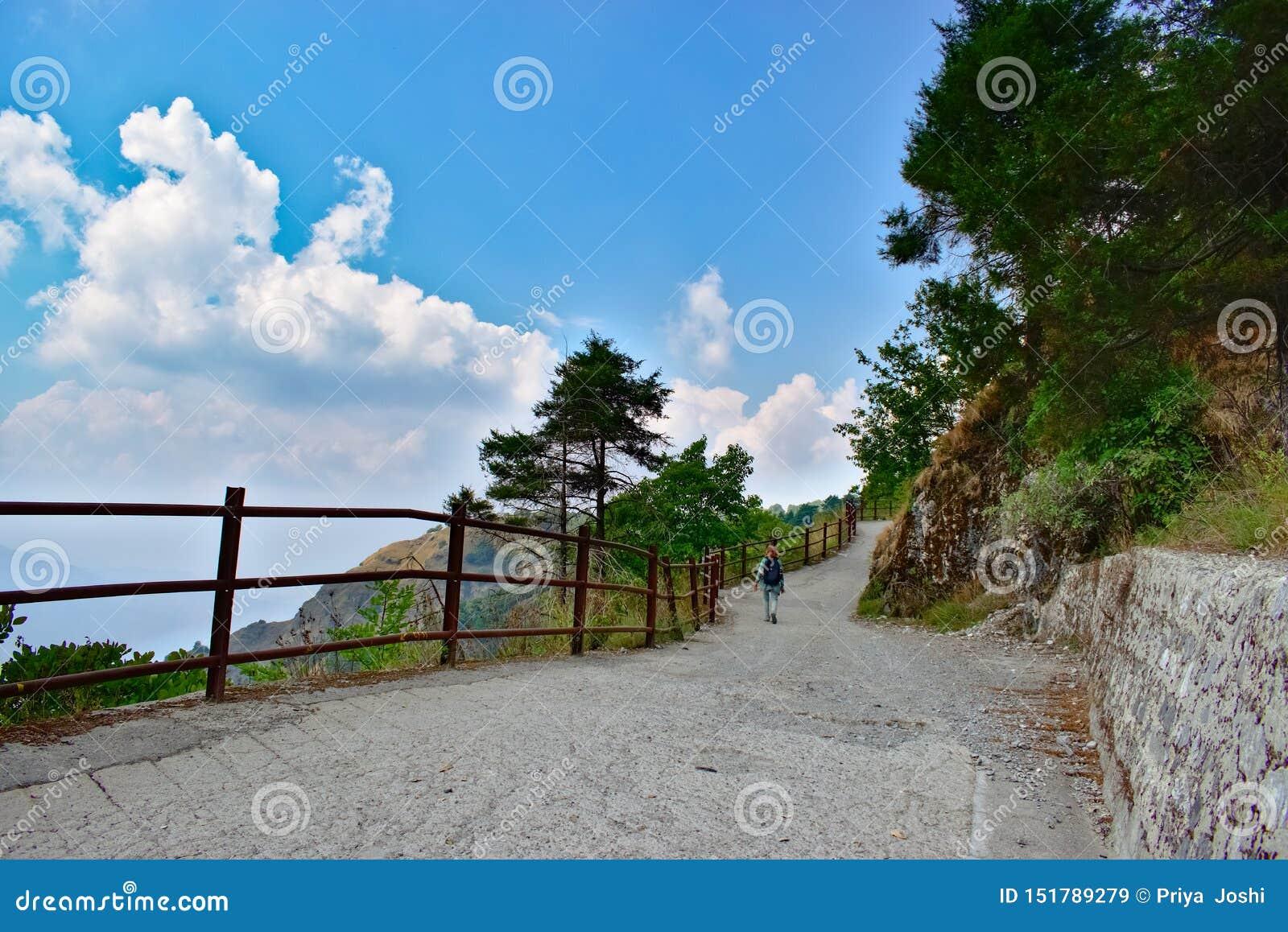 Женщина с красными волосами самостоятельно в горах с красивыми облаками trekking самостоятельно в лесе с пейзажем красивого вида
