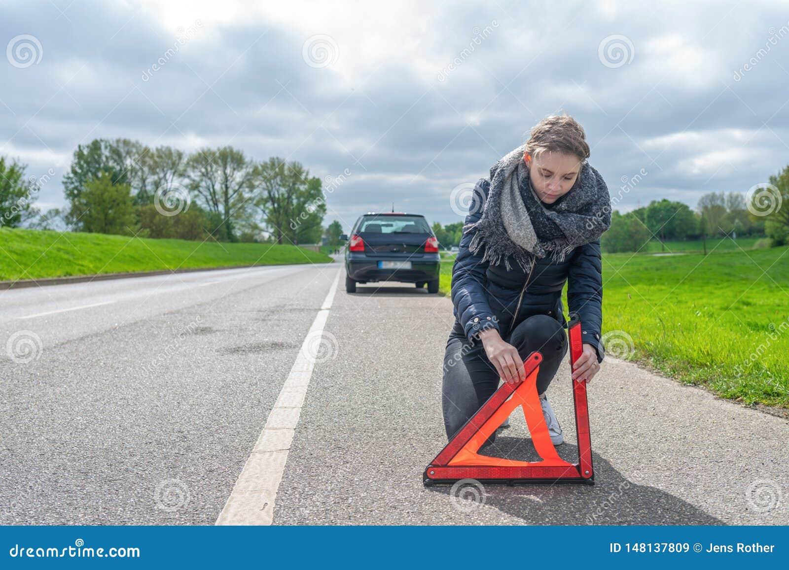 Женщина с нервным расстройством автомобиля кладет предупреждающий треугольник на улицу