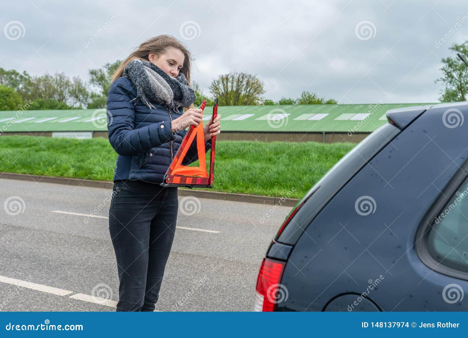 Женщина с нервным расстройством автомобиля установила предупреждающий треугольник за ее автомобилем