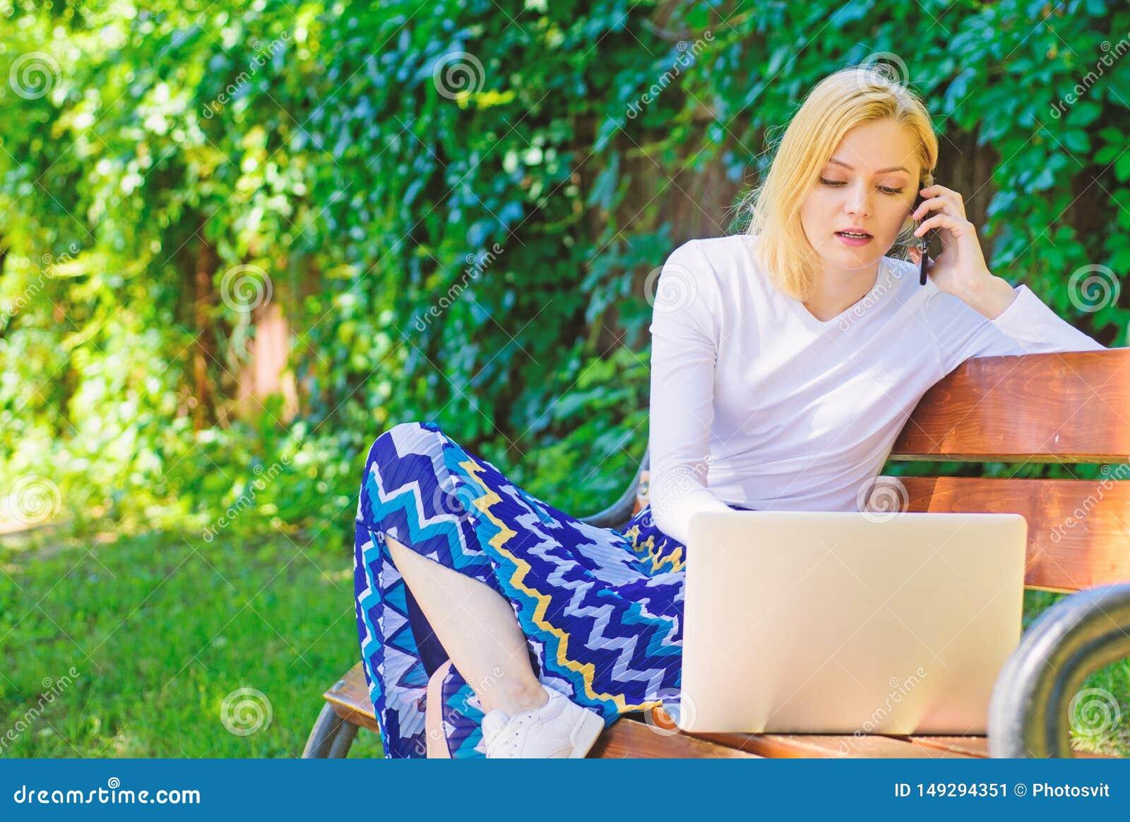 Женщина с ноутбуком работает на открытом воздухе зеленая предпосылка природы Удаленные работы просматривают верхние независимые у