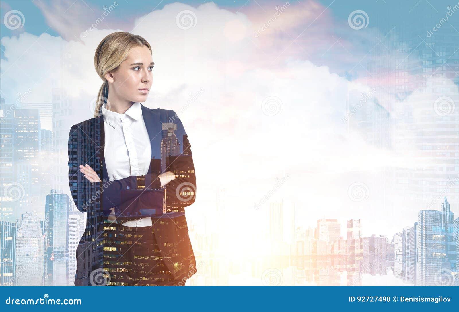 Женщина с пересеченными оружиями в солнечном городе