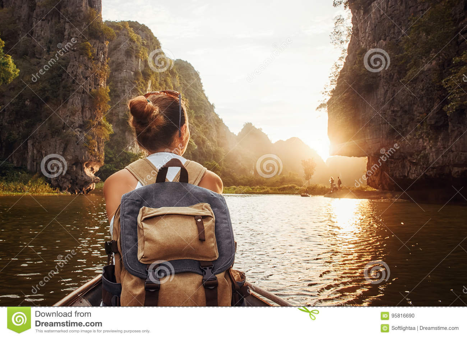 Женщина с рюкзаком путешествуя шлюпкой наслаждаясь заходом солнца среди m