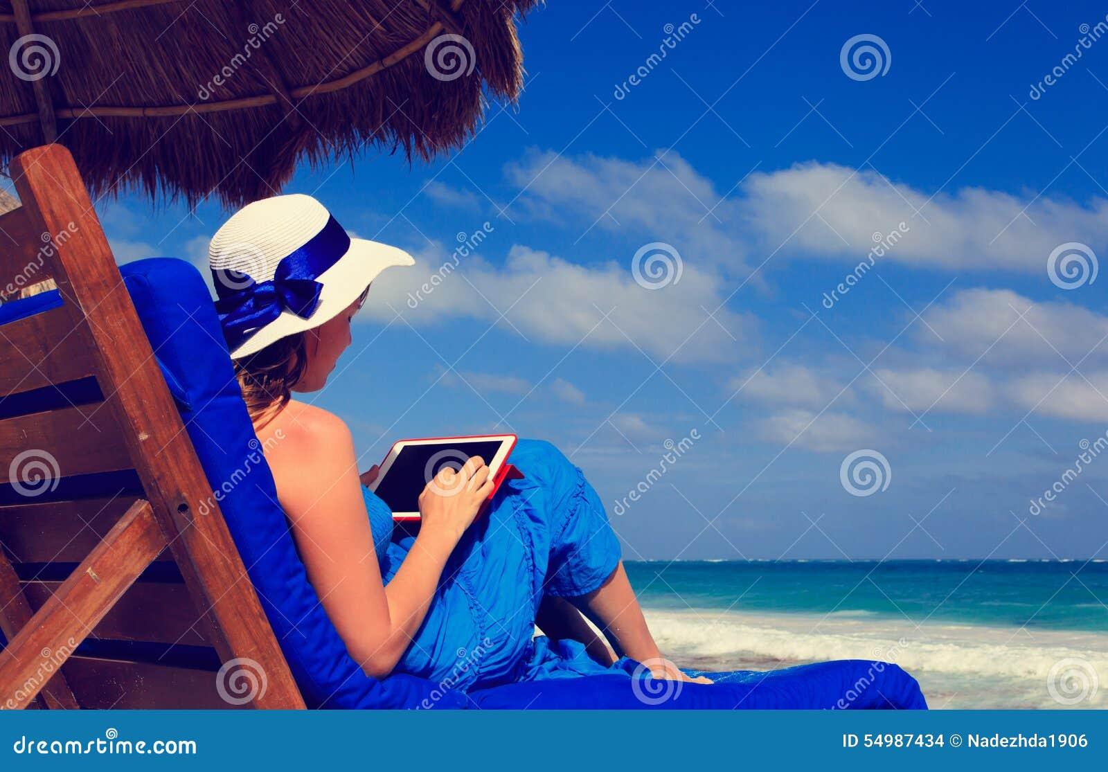 Женщина с сенсорной панелью на тропическом пляже