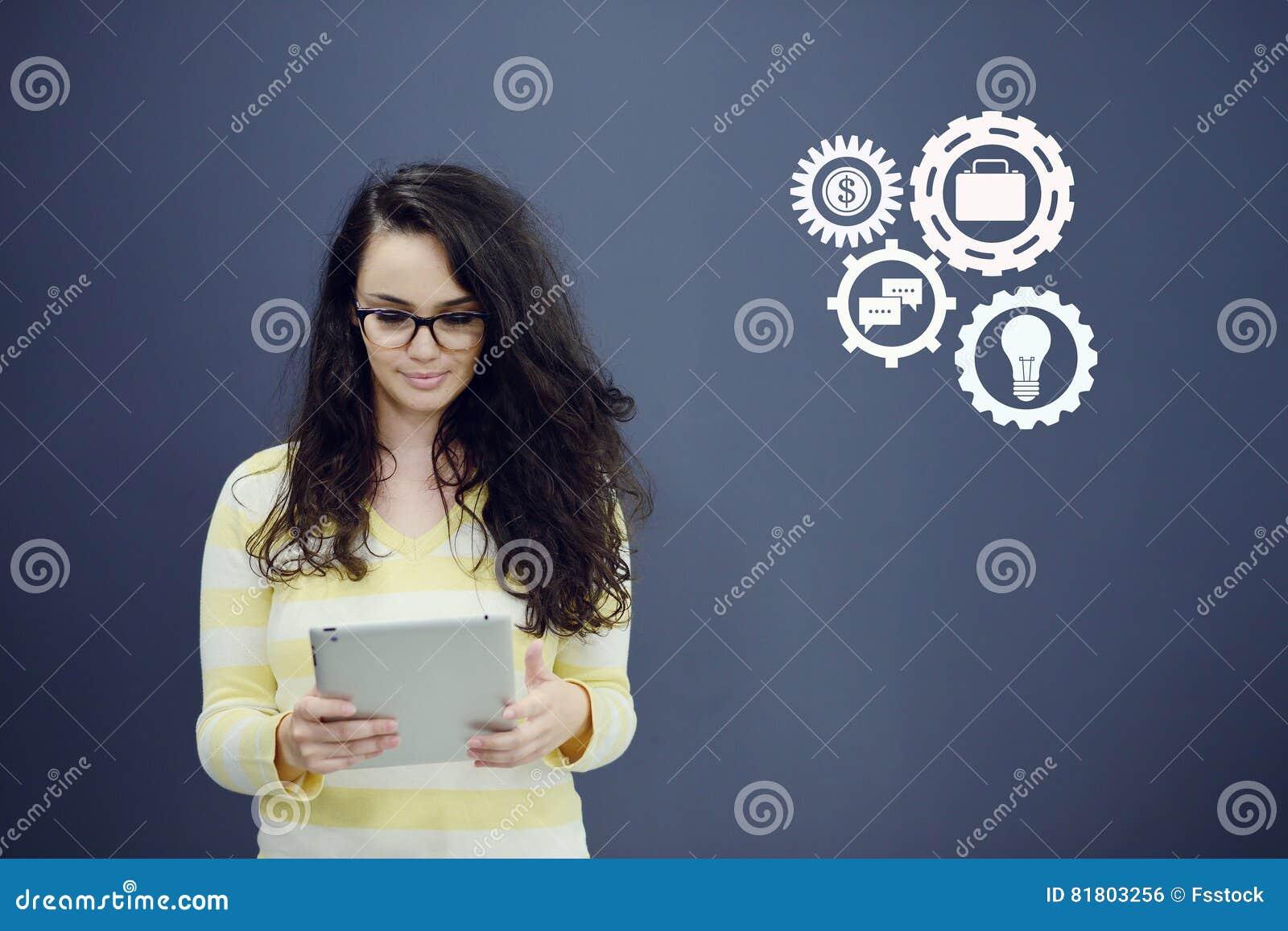 Женщина с таблеткой перед предпосылкой с вычерченными диаграммой и значками дела