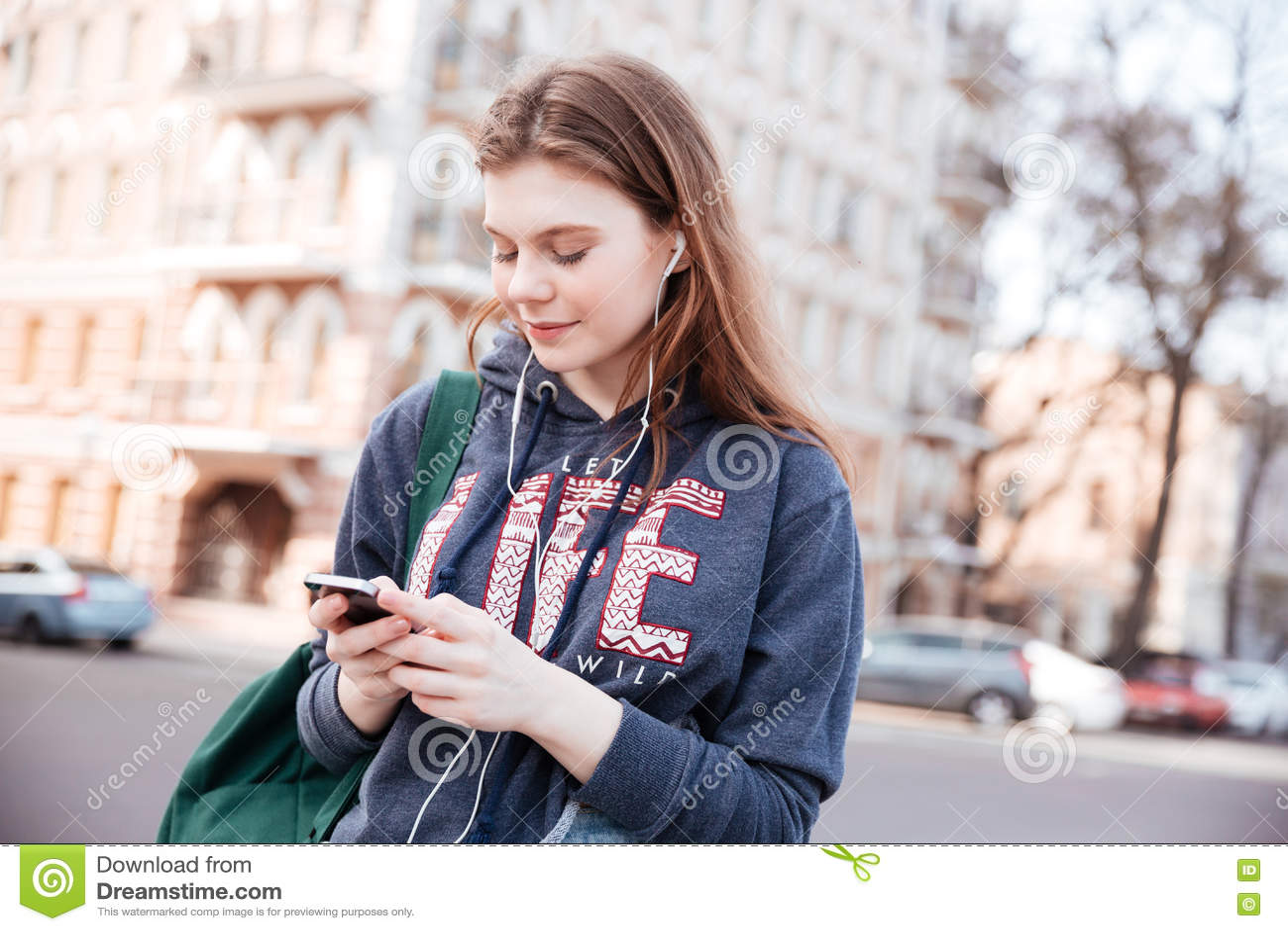 Download Женщина слушая к музыке и используя сотовый телефон на улице Стоковое Фото - изображение насчитывающей посылка, способ: 72292390