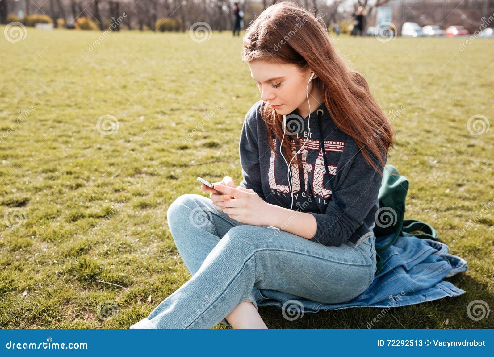 Download Женщина слушая к музыке от Smartphone сидя на траве Стоковое Изображение - изображение насчитывающей отражательно, подлинный: 72292513