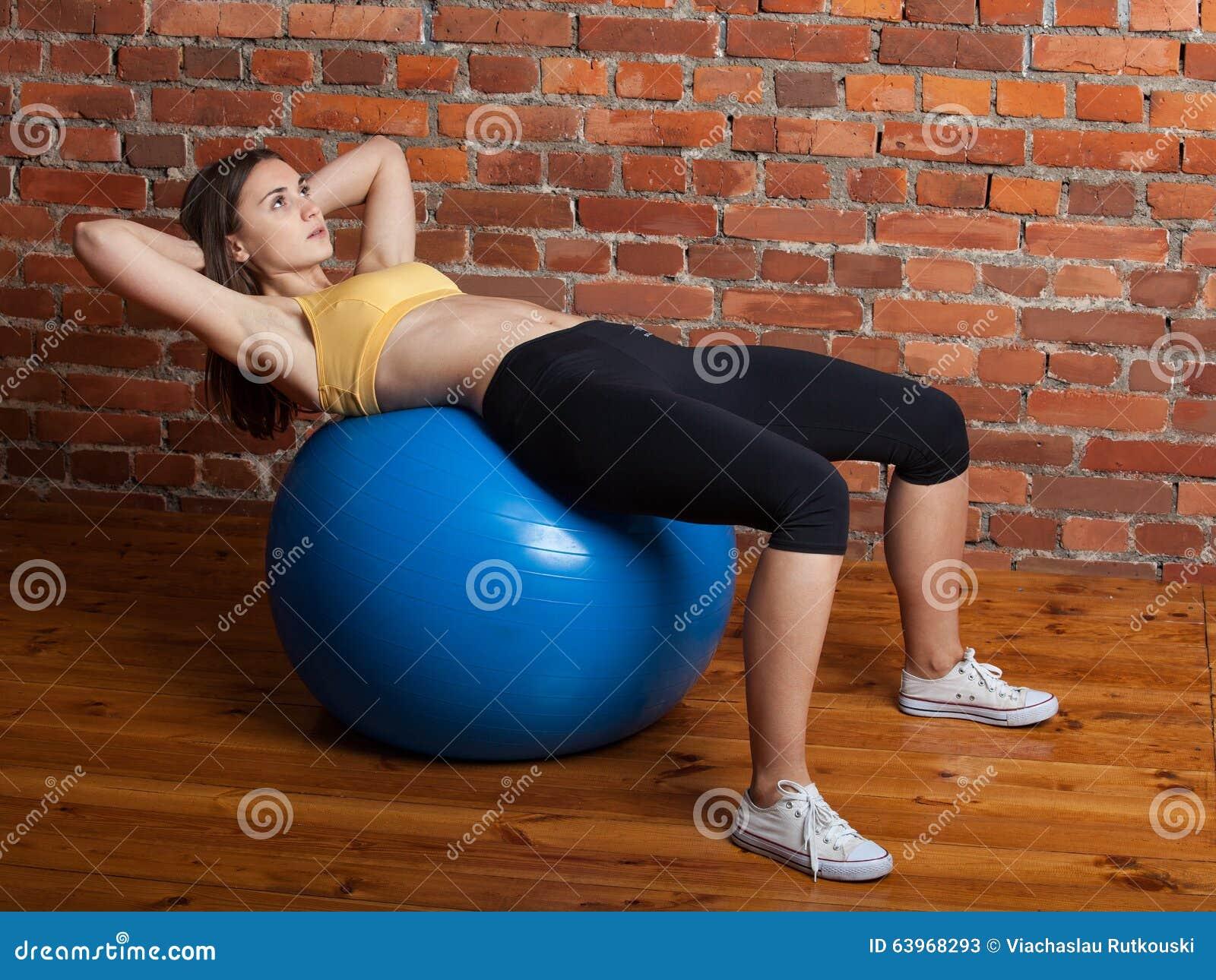 Женщина трясет прессу на шарике на фоне b