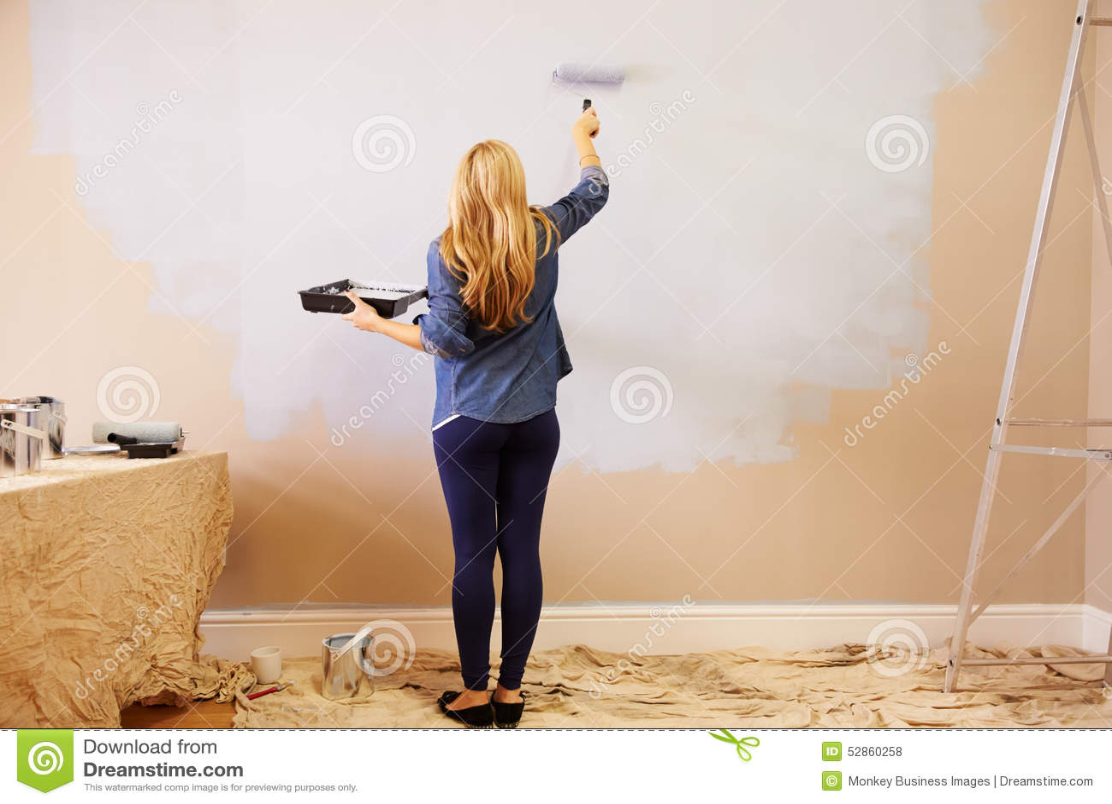 Женщина украшая комнату используя ролик краски на стене