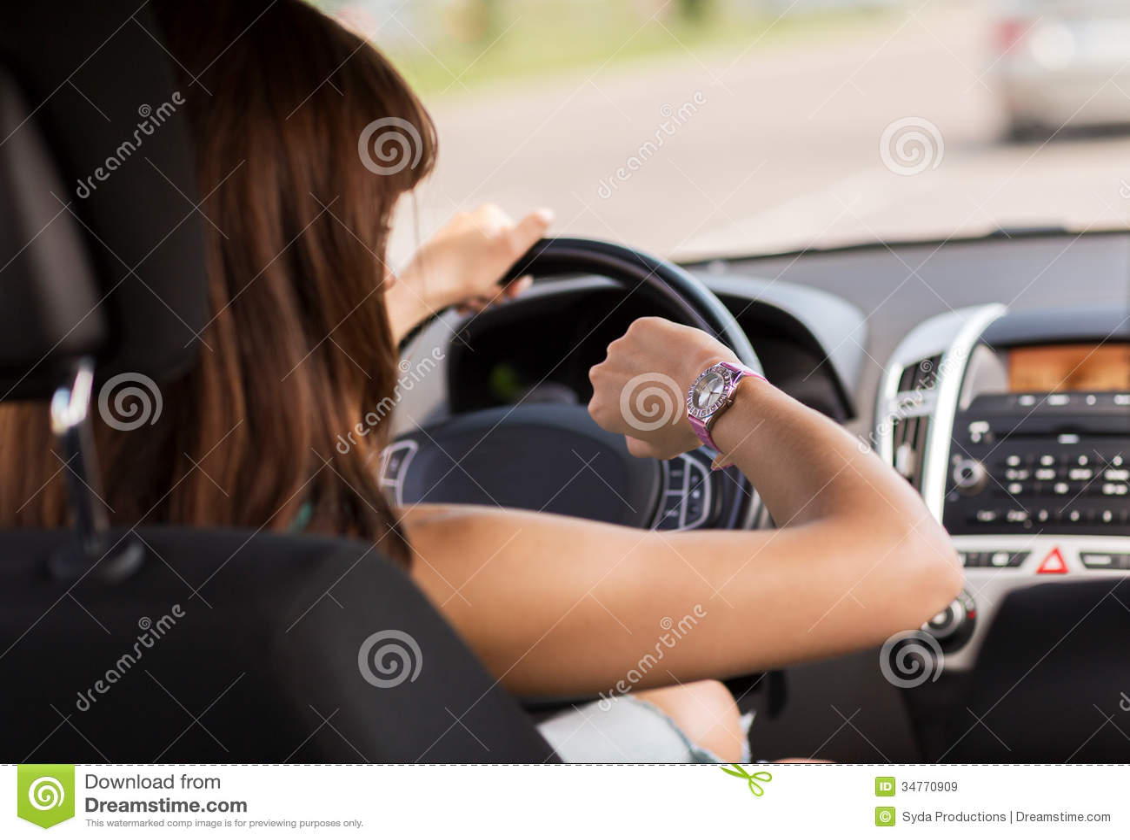 Женщина управляя автомобилем и смотря вахту