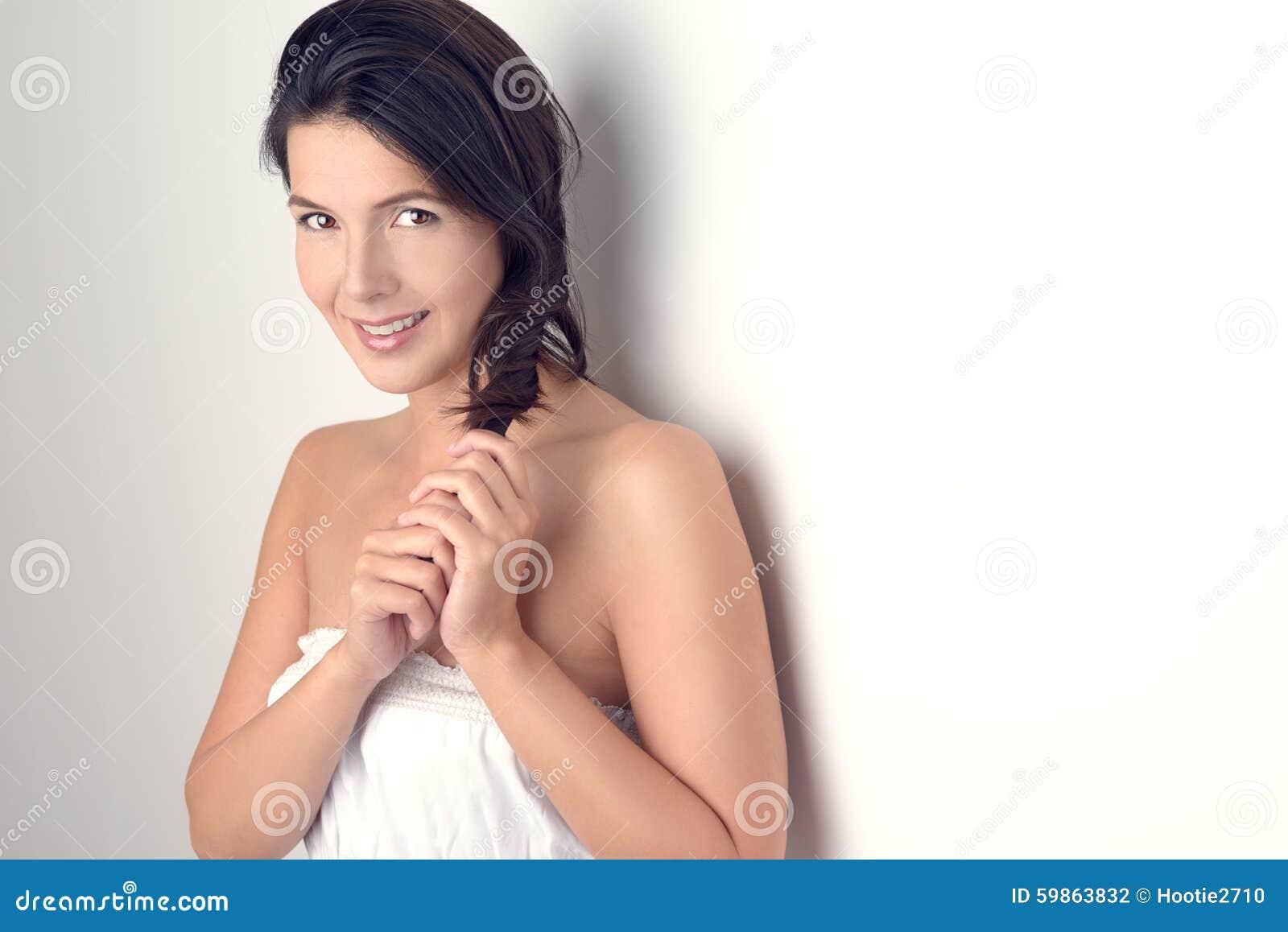 Женщина усмехаясь на камере пока держащ ее волосы