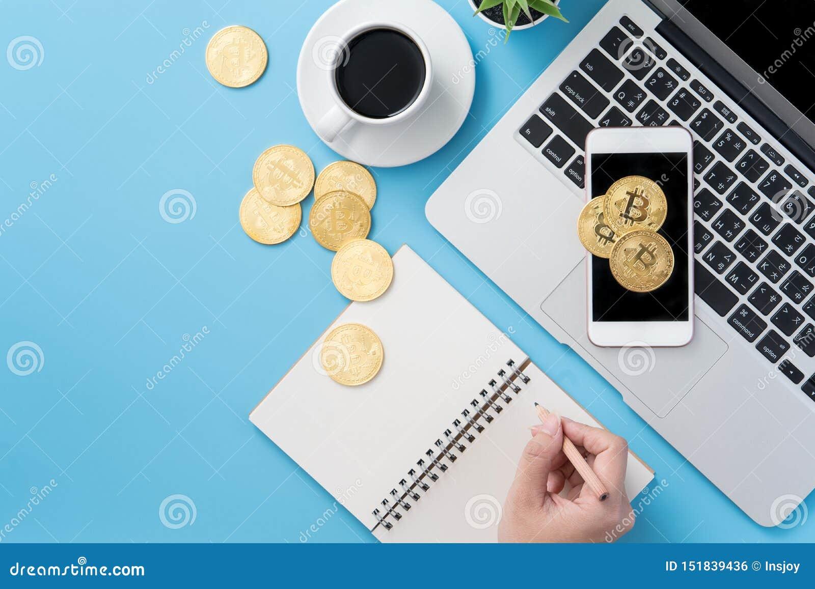 Женщина учитывающ концепция денег изолируется на столе чистого голубого офиса работая с bitcoin и кофейной чашкой, дизайном места
