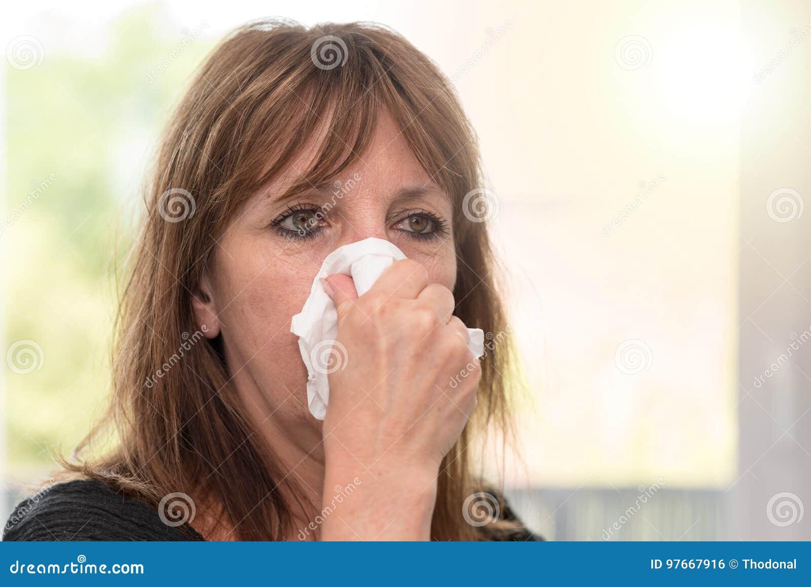 Женщина дуя ее нос, световой эффект